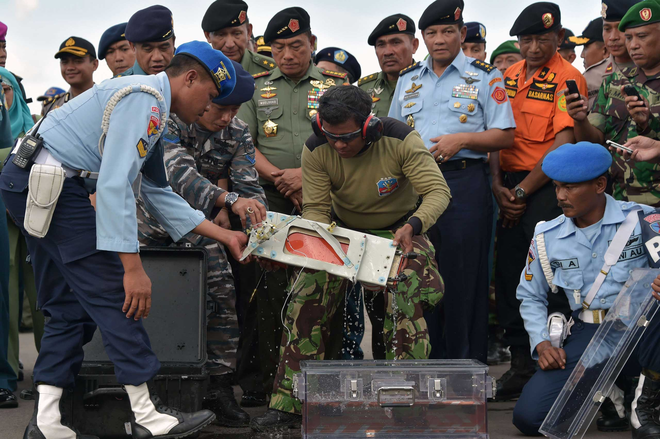 Jan. 12, 2015. Indonesian officers move the flight data recorder of the AirAsia flight QZ8501 that went down with 162 passengers into a suitable protective transportation case in the town of Pangkalan Bun in Indonesia after it was retrieved from the Java Sea.