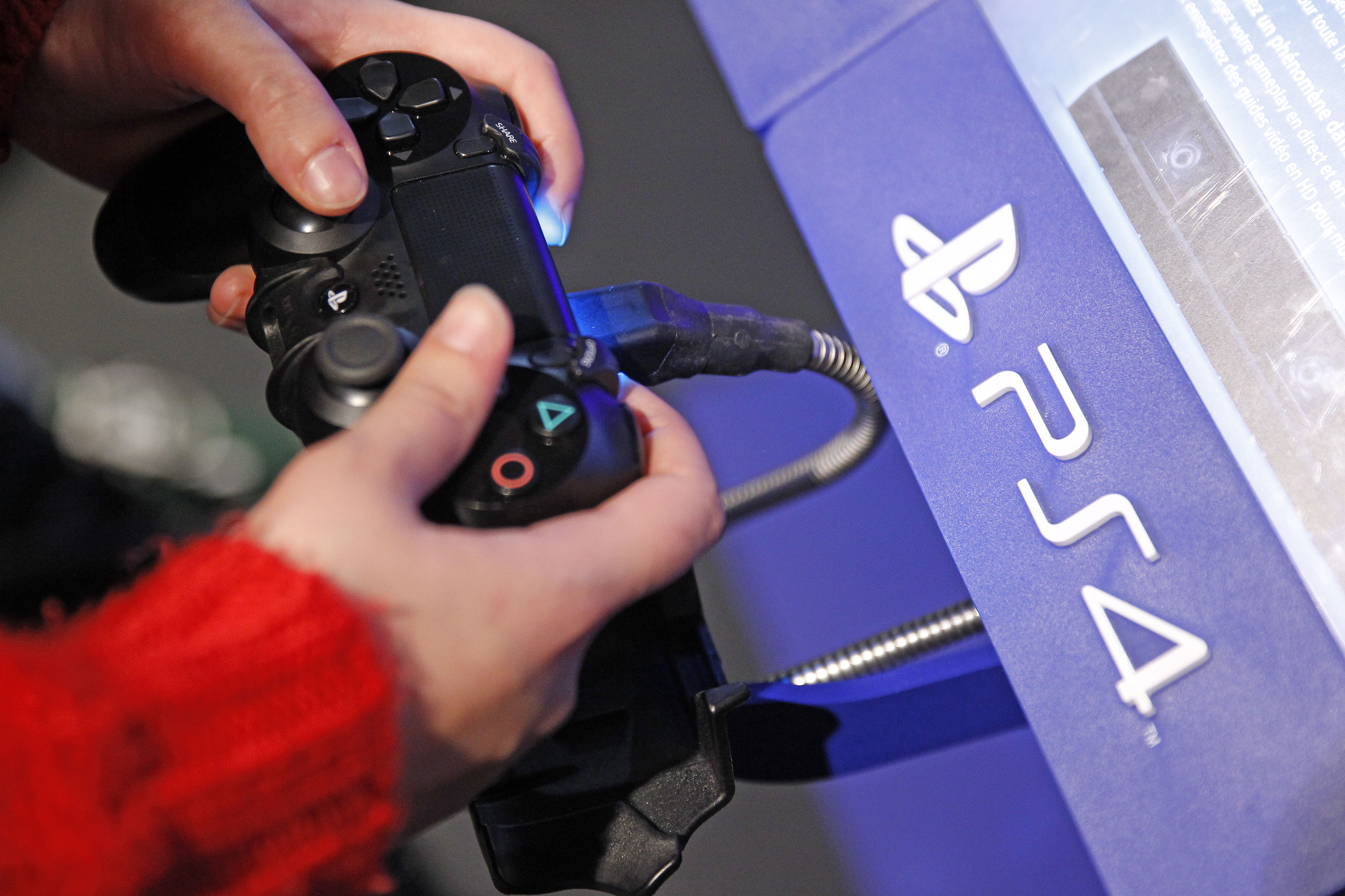 A visitor plays on Sony Playstation 4 video game console (PS4), produced by Sony Corp during the 'Noel de Geek' at the Cite des Sciences et de l'industrie on Dec. 23, 2014 in Paris, France.