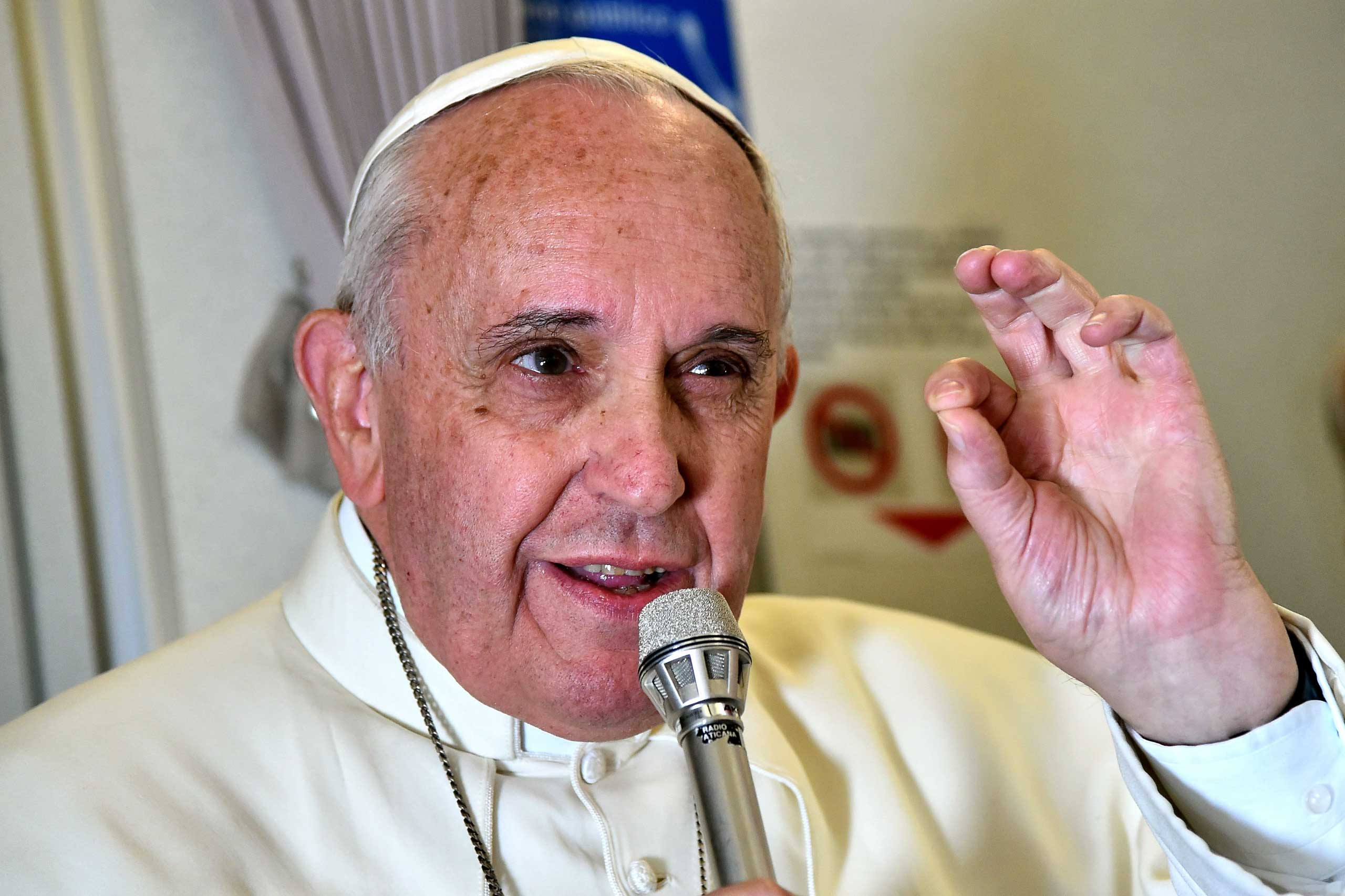 Pope Francis adresses journalists sitting onboard a plane during his trip back to Rome, on Jan. 19, 2015.