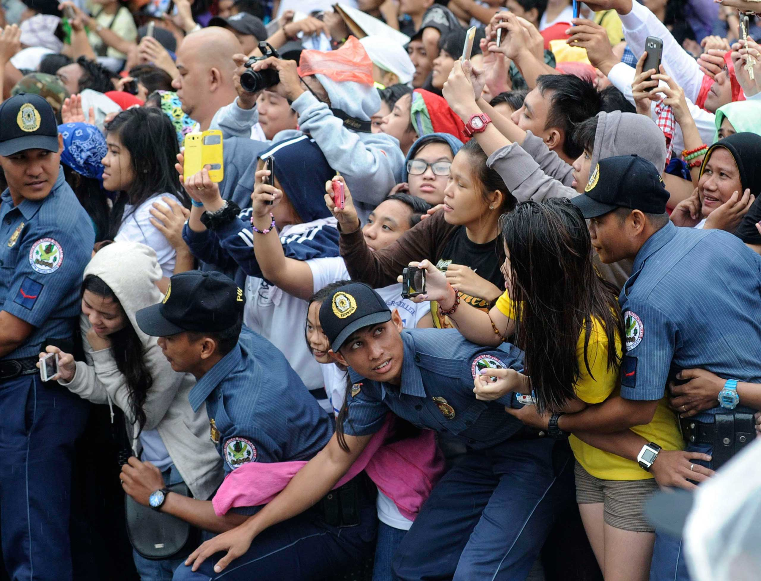 Members of the Philippine National Police prevent well-wishers from moving forward as Pope Francis' motorcade passes by in Manila, Jan. 18, 2015.