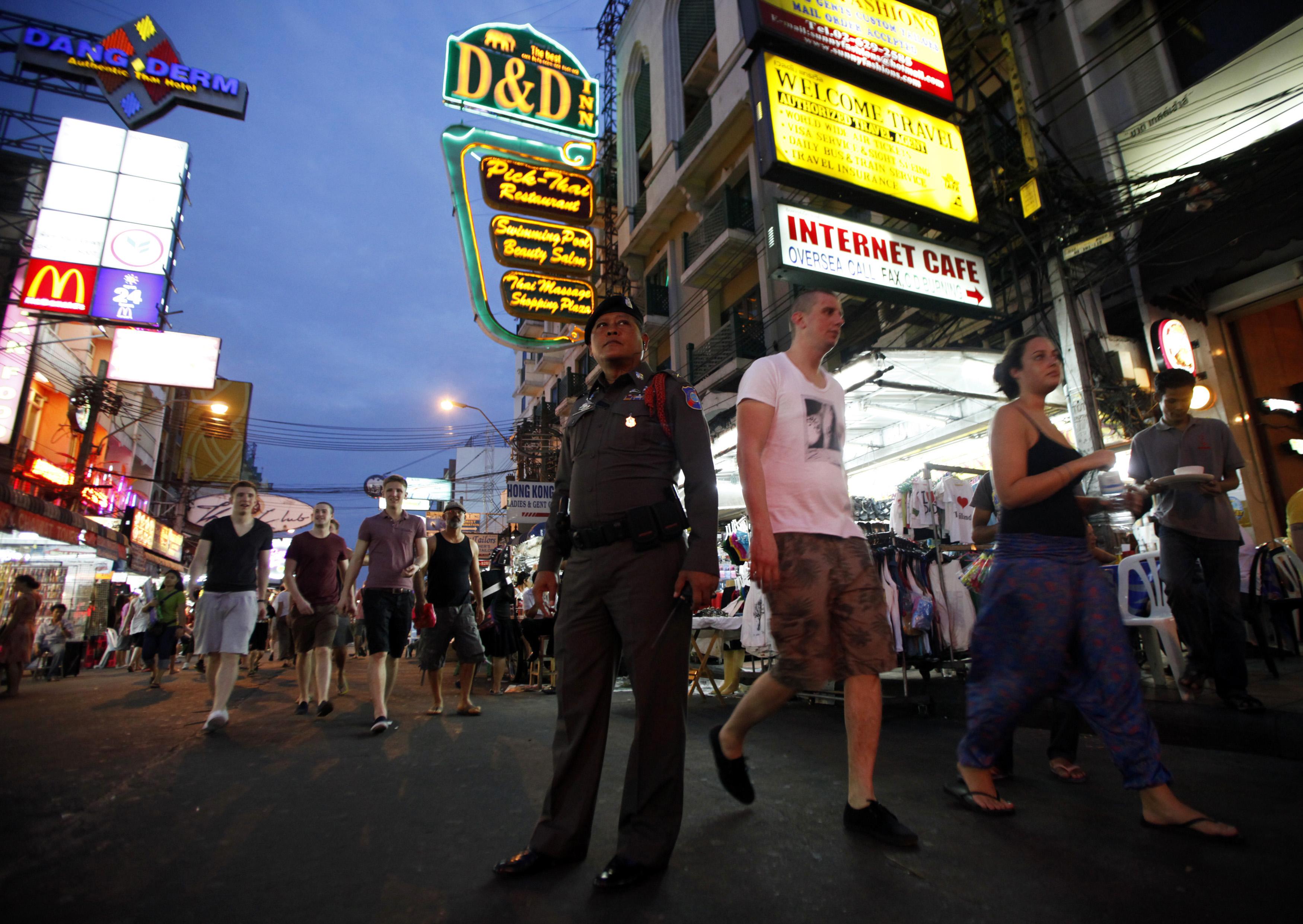 A policeman stands guard as tourists walk along Khaosan Road in Bangkok on Jan. 19, 2012