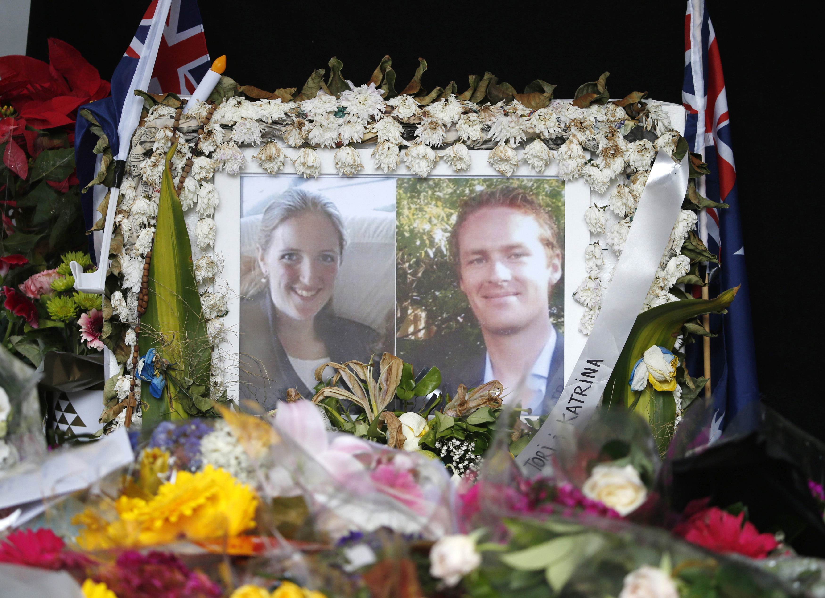 Photographs of the Sydney siege victims, lawyer Katrina Dawson, left, and café manager Tori Johnson, are displayed near the site of the siege in Sidney's Martin Place on Dec. 23, 2014