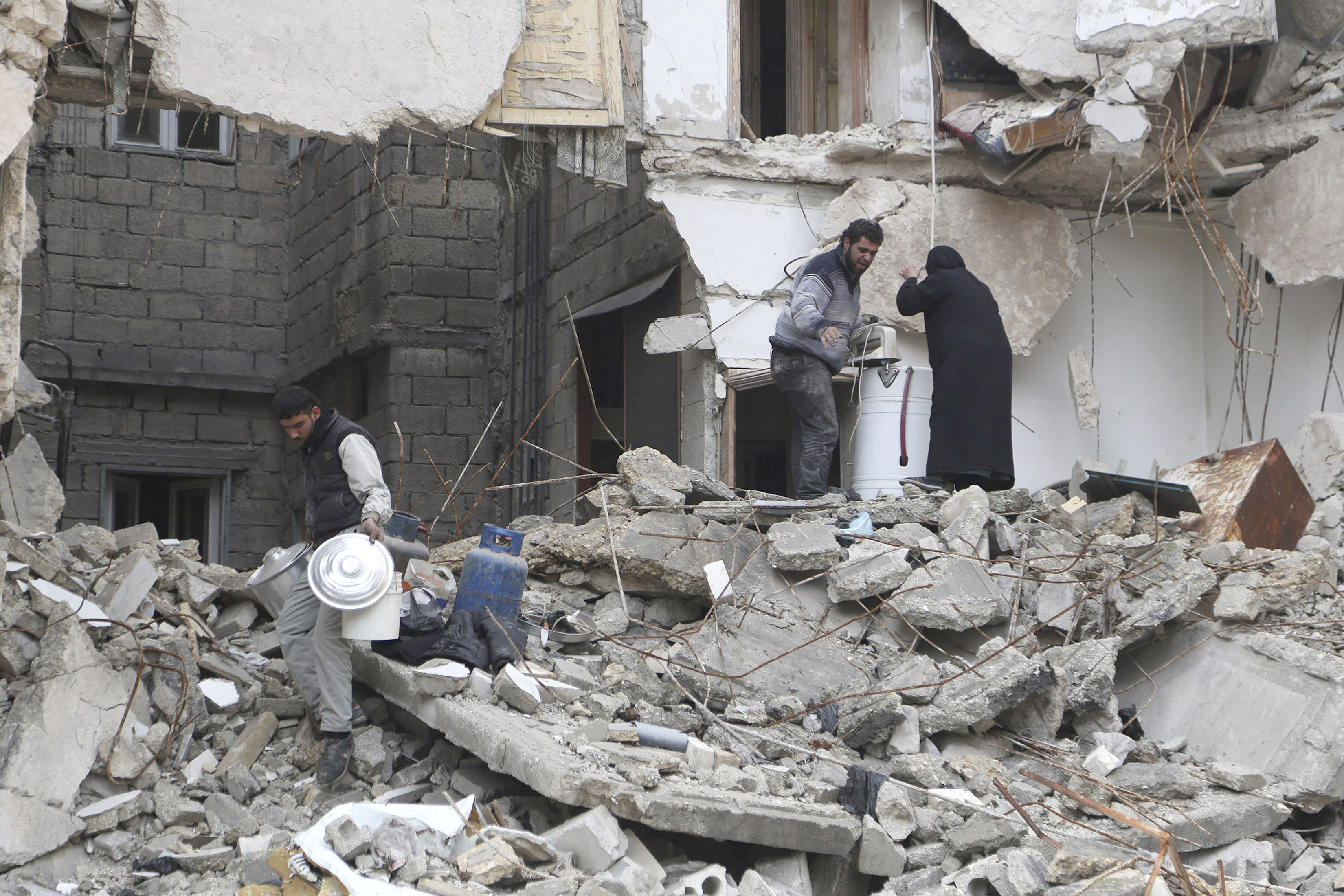 Residents look for belongings amid debris of a collapsed building in Aleppo December 31, 2014.
