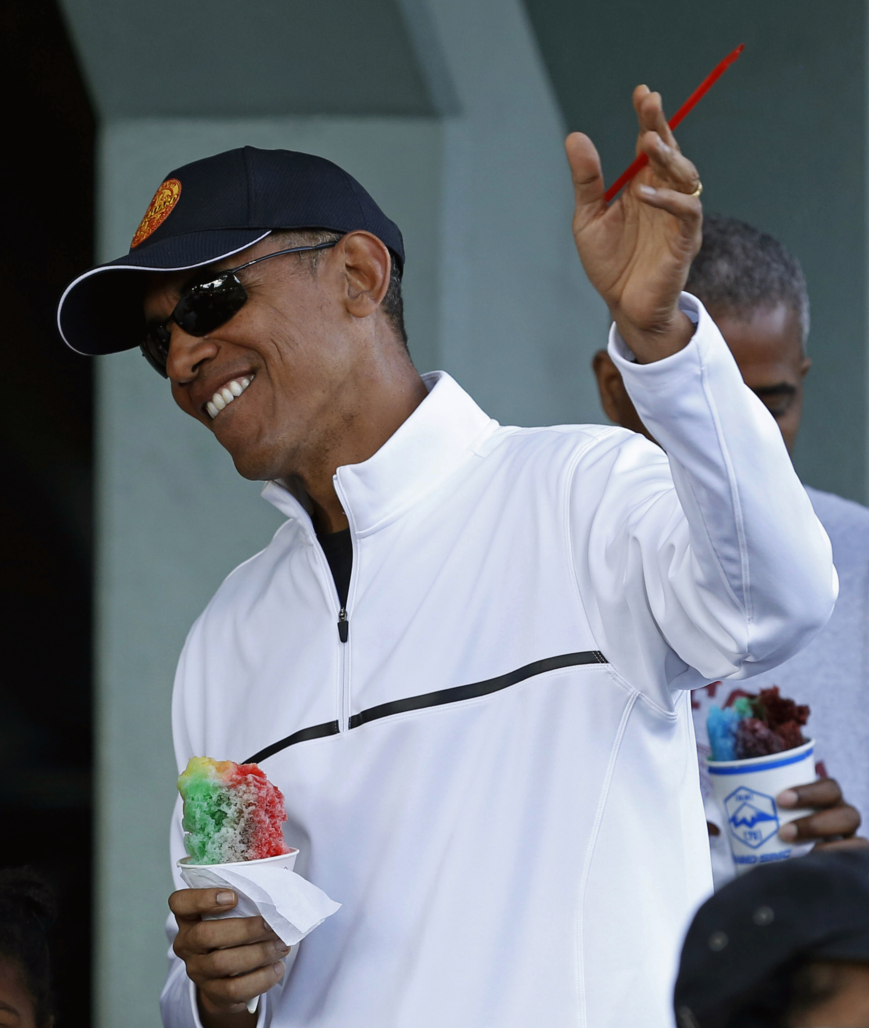 U.S. President Barack Obama waves to people while enjoying a shave ice at Island Snow in Kailua, Hawaii January 1, 2015.