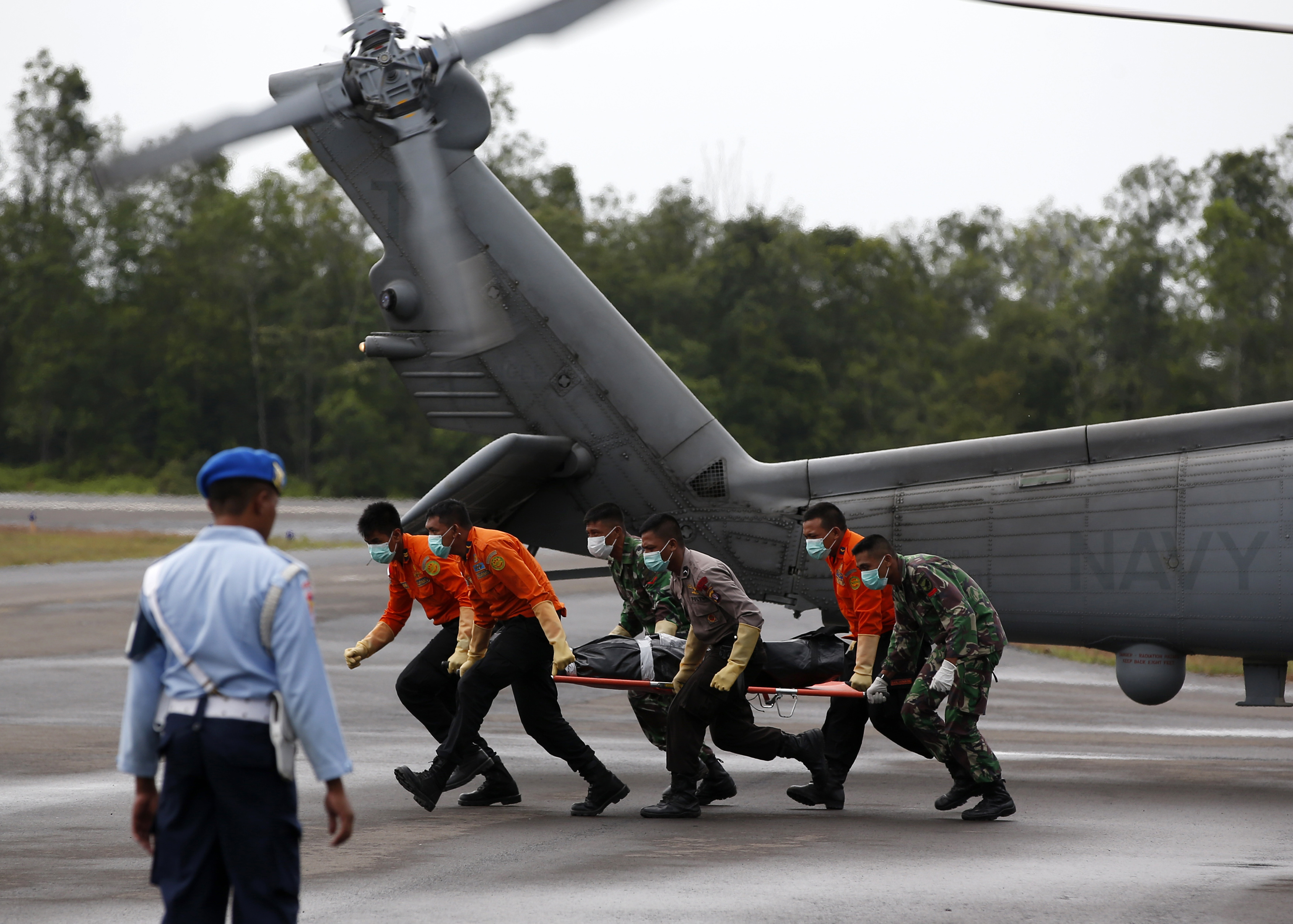 The body of an AirAsia QZ 8501 passenger is carried to an ambulance after being transported from a ship by a U.S. Navy helicopter from the U.S.S. Sampson at the air base in Pangkalan Bun, in Indonesia's Central Kalimantan, on Jan. 4, 2015