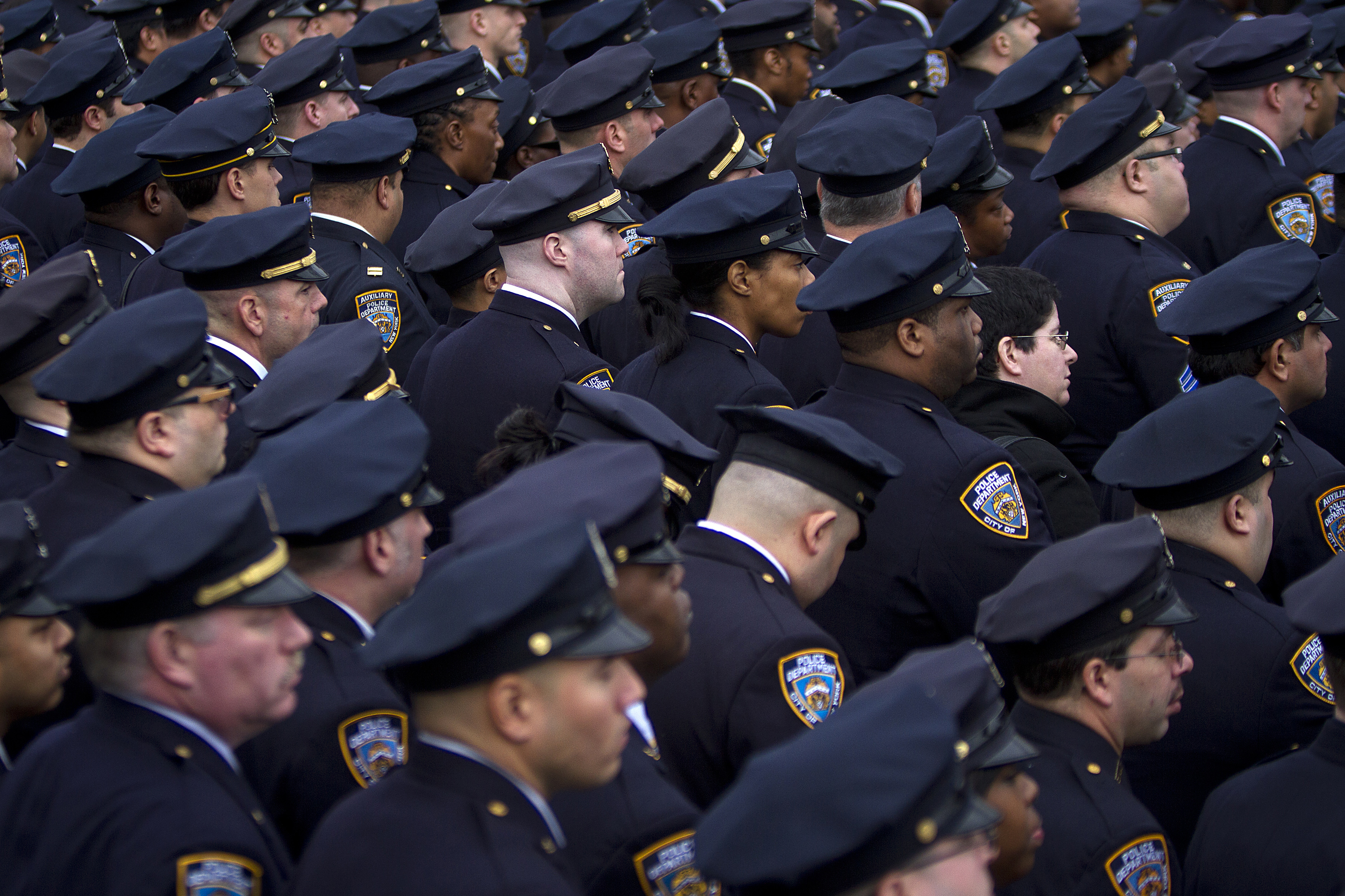 Police officers from the 84th Precinct listen during the funeral for slain New York Police Department officer Wenjian Liu in the Brooklyn borough of New York January 4, 2015.