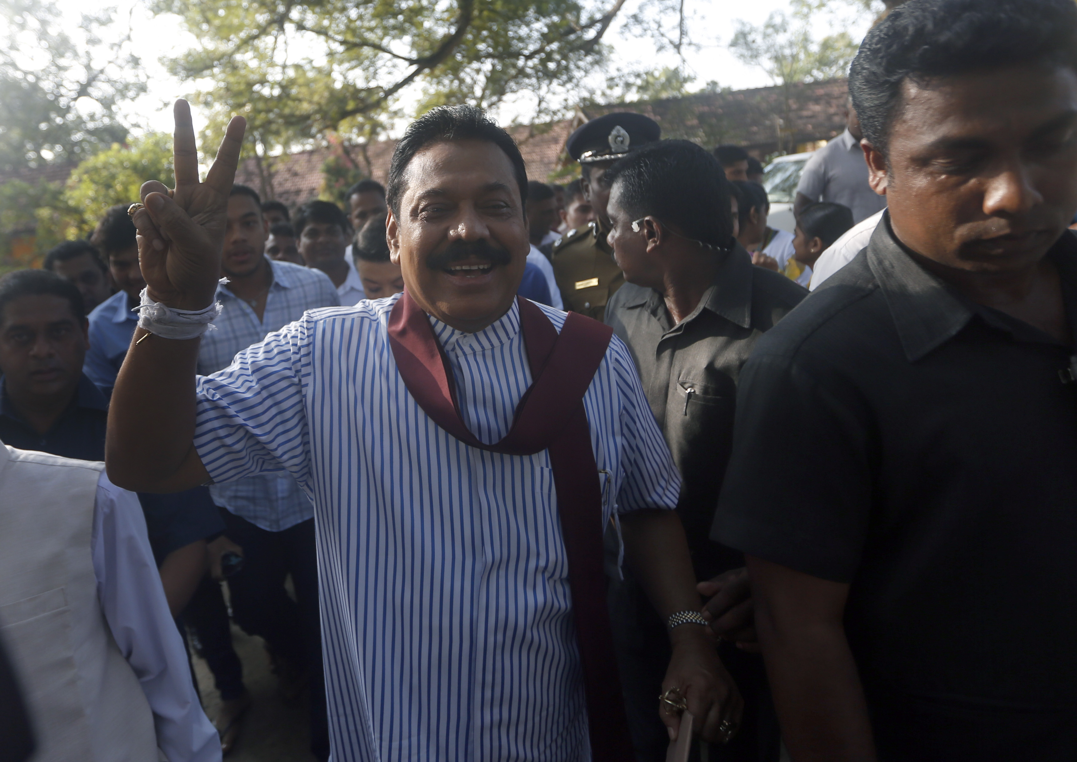 Sri Lanka's President Mahinda Rajapaksa gestures to the media after casting his vote for the presidential election, in Medamulana, January 8, 2015.