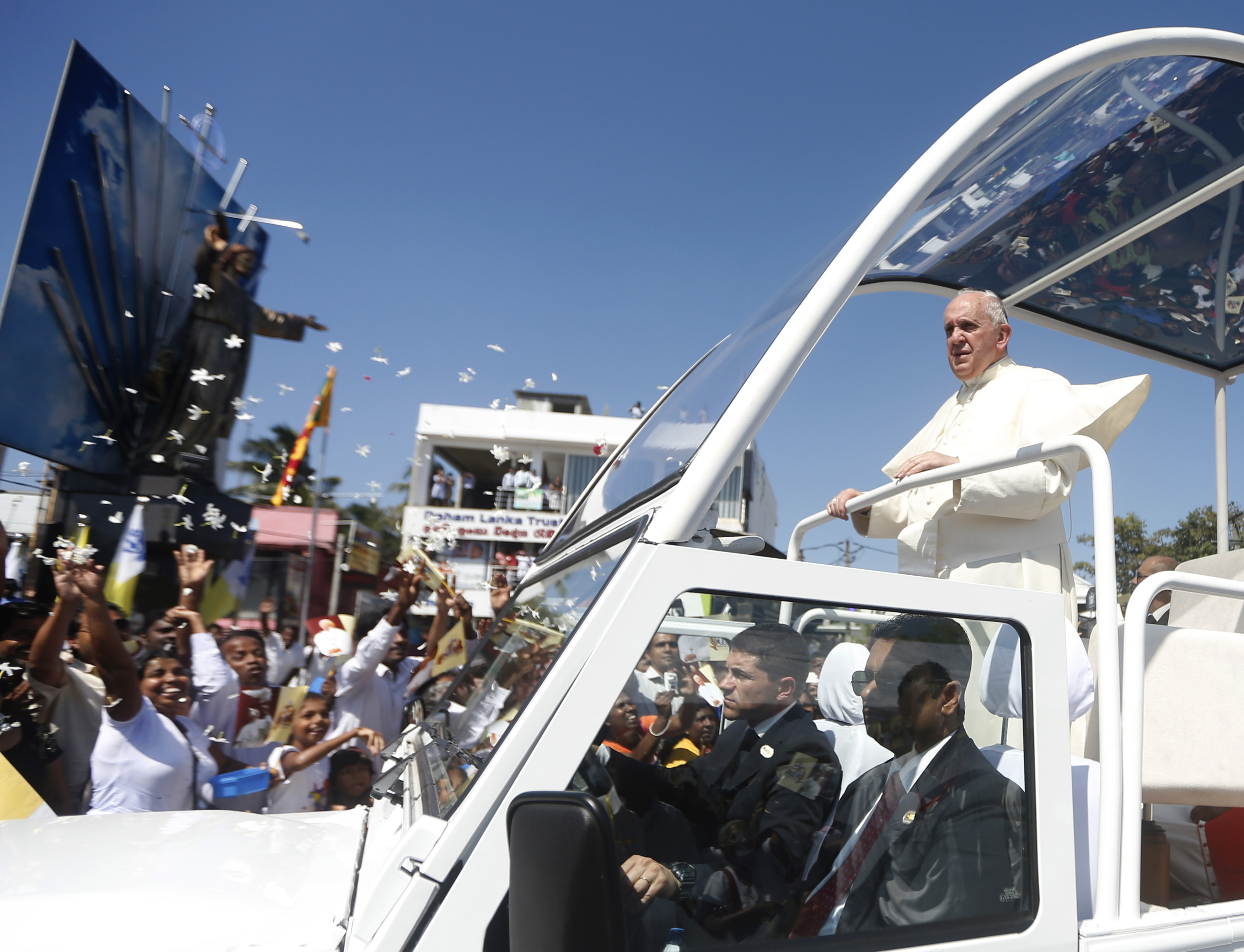 Pope Francis stands on his vehicle as devotees gather on the road to see him after he arrived at the Colombo airport Jan. 13, 2015