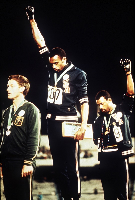 Gold medalist Tommie Smith (C) and bronze medalist John Carlos give the black power salute on the podium during the 1968 Olympic Games