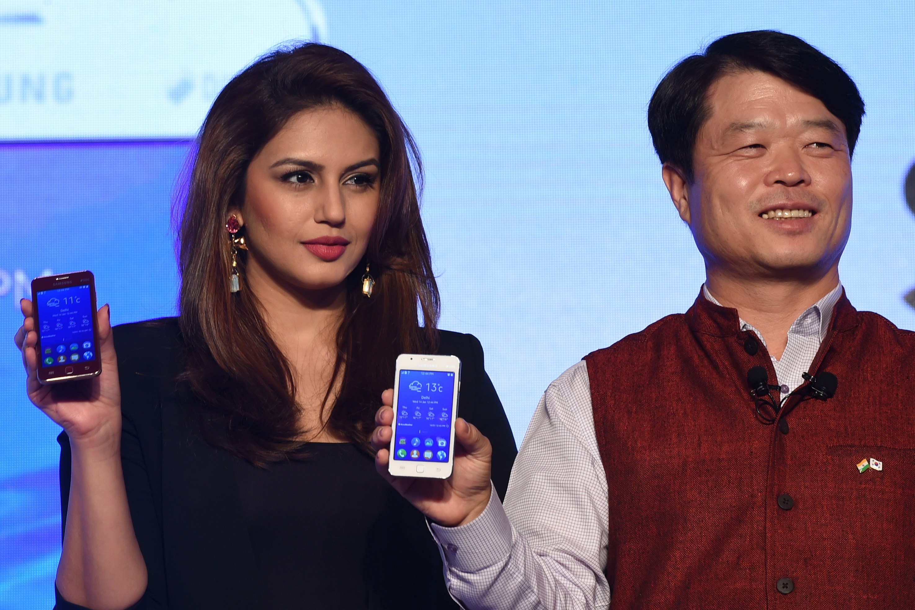 Indian Bollywood actress Huma Qureshi poses with Hyun Chil Hong, president and CEO of Samsung India, during the launch of the Samsung Z1 smartphone at a function in New Delhi on Jan. 14, 2015.