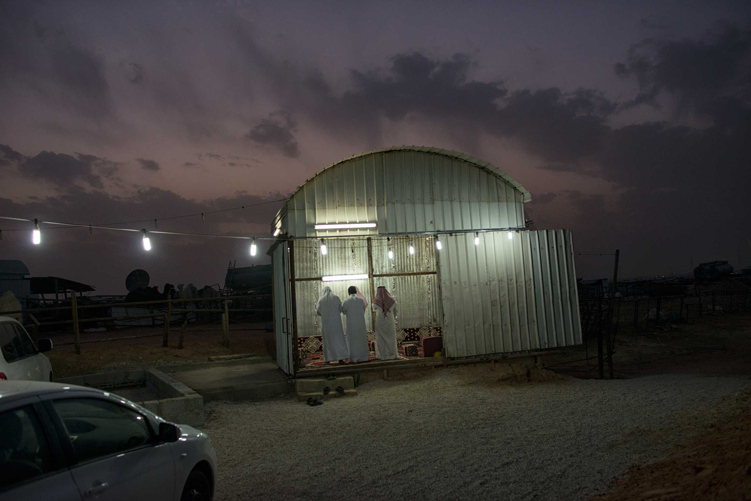 Saudi men pray at dusk at a camel market outside of Riyadh.