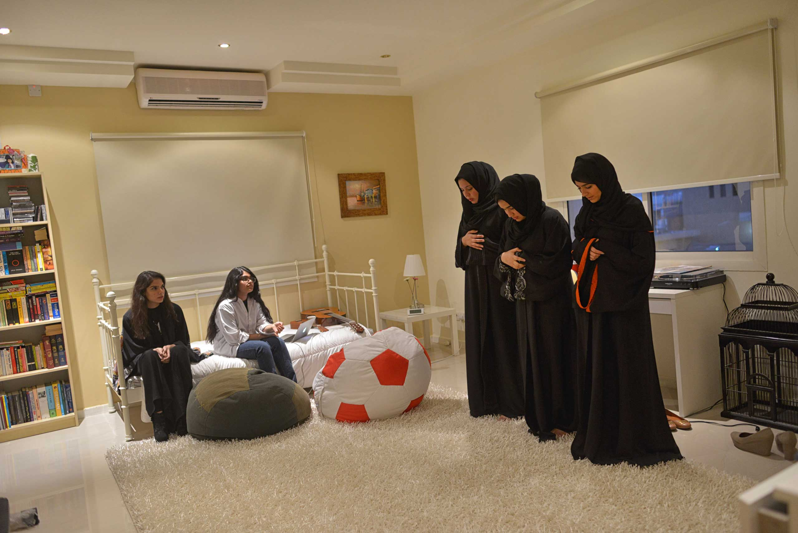Young Saudi women pray in a friend's home before going out to dinner in Riyadh. Though statistics are difficult to confirm, youth unemployment and poverty are on the rise in Saudi Arabia. While society is increasingly open to women in the workforce, there are still limited jobs in which women and men can work side by side. There are a great number of highly educated Saudis who can not find work suitable for their qualifications.