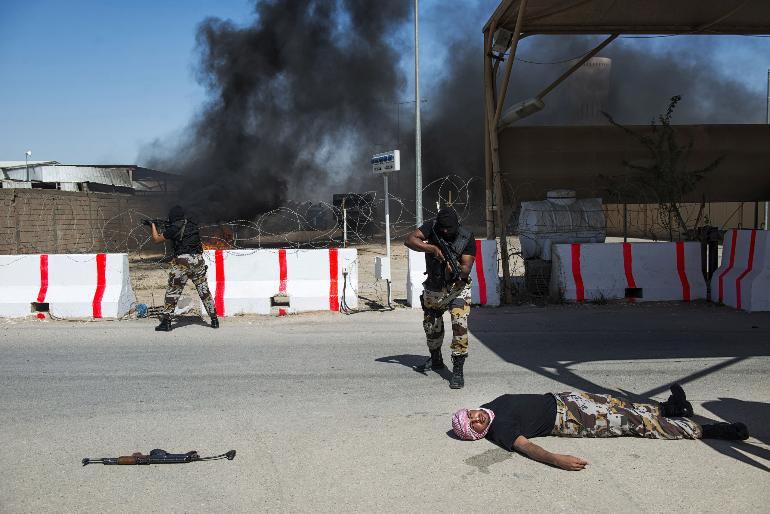 Troops with the Saudi Special Security Forces pretend to execute a terrorist during a simulated attack on a compound at the Counter-Terrorism Training School camp, March 5, 2013.