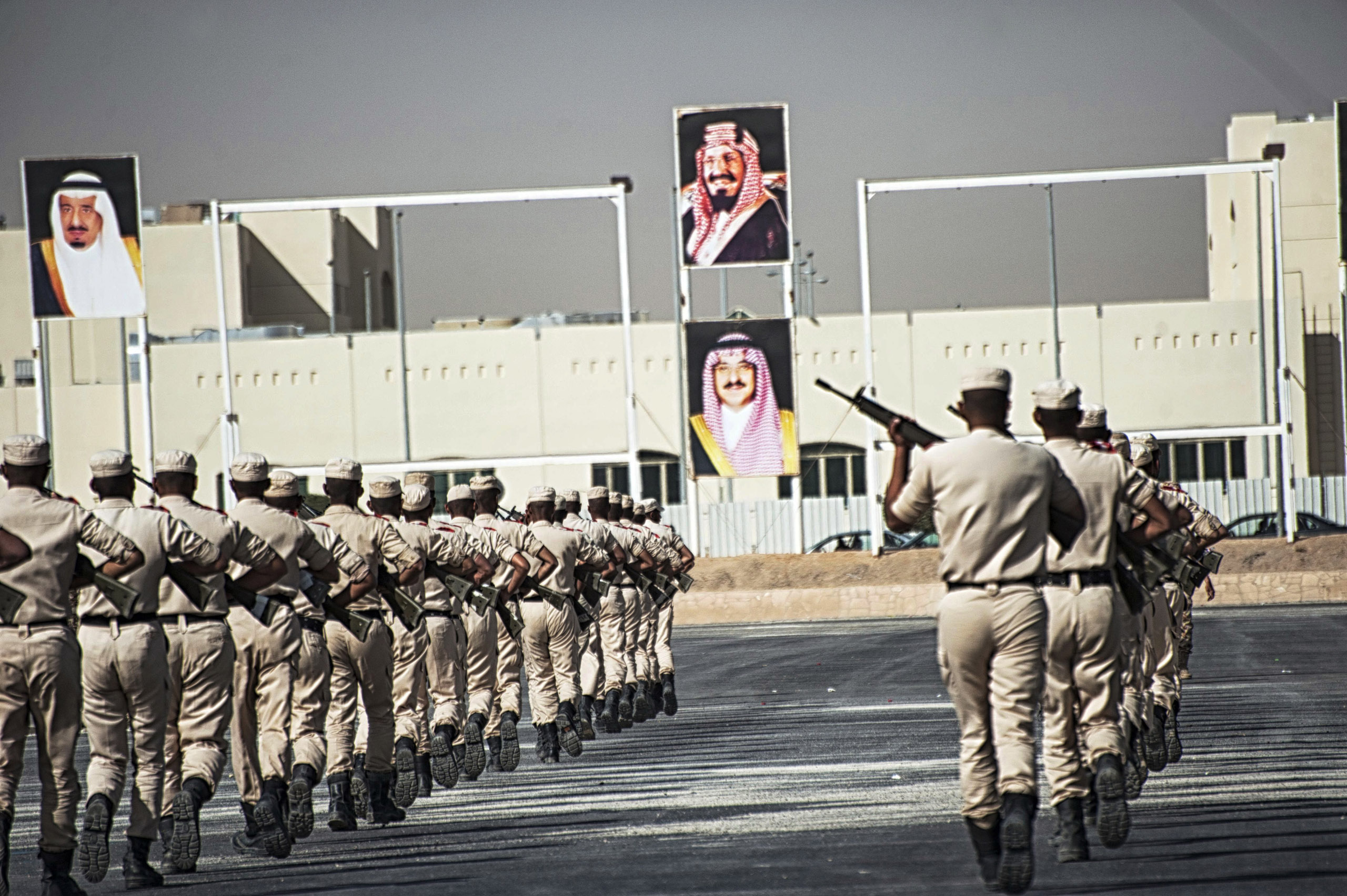 Troops with the Saudi Special Security Forces perform a show of force below images of the Royal family, from left: King Salman bin AbdulAziz, King AbdulAziz, Prince Mohammed bin Nayef, at the Counter-Terrorism Training School camp, March 5, 2013.