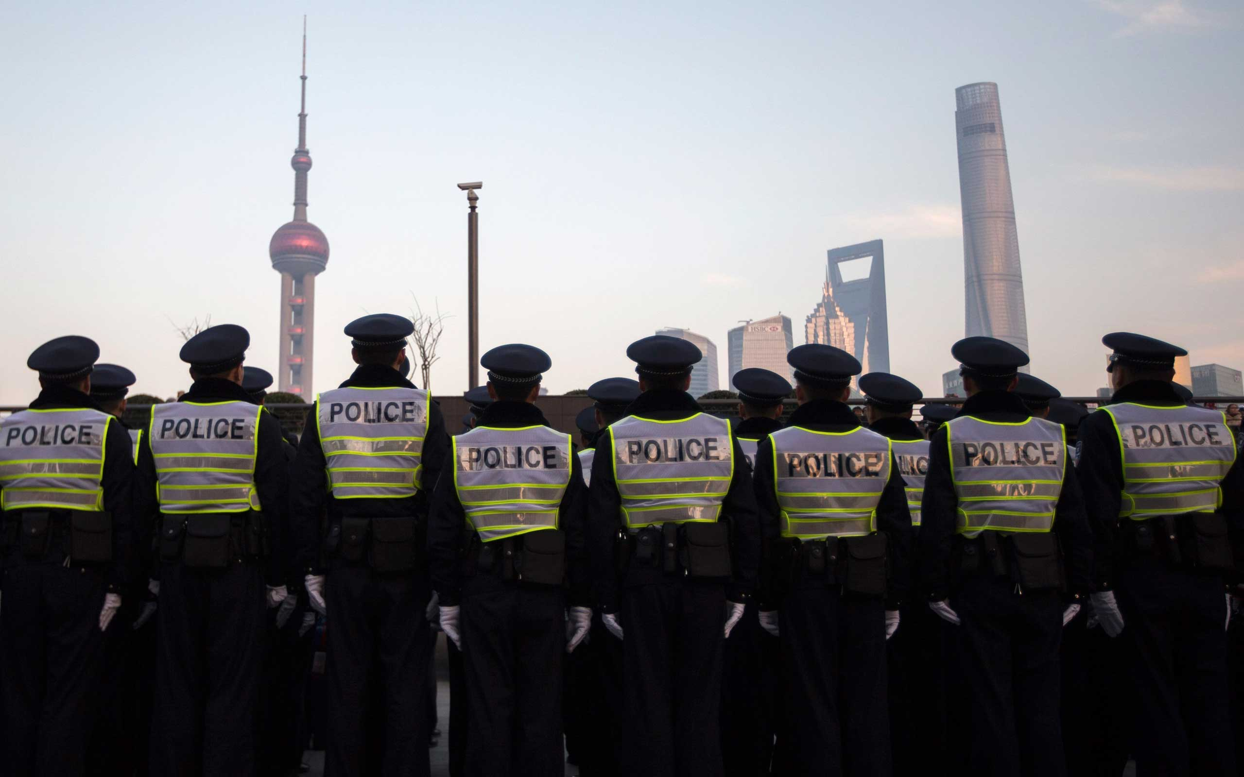 Policemen stand in formation as they guard on the bund where people were killed in a stampede incident during a new year's celebration, in Shanghai on Jan. 3, 2015.