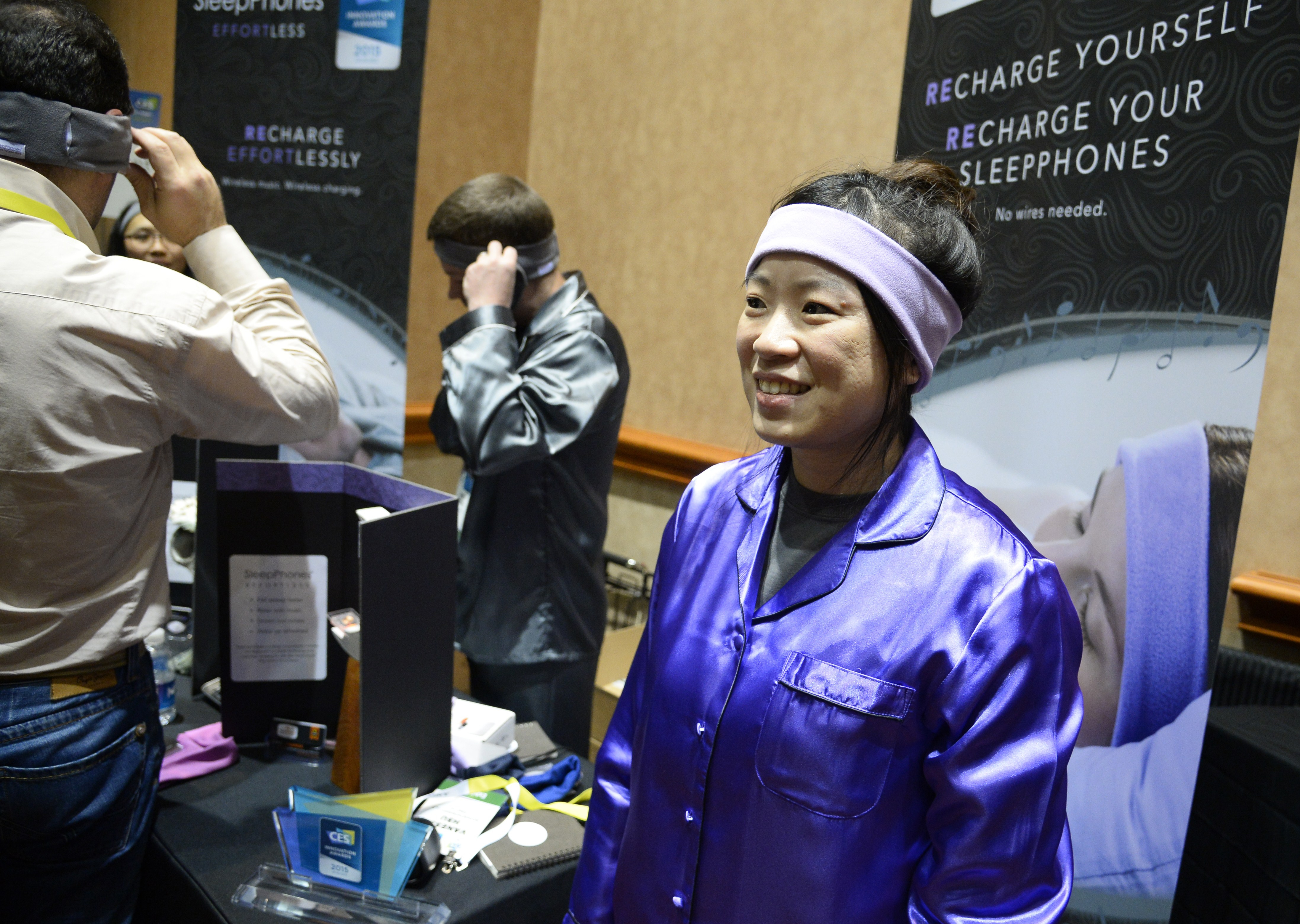 Dressed in pajamas, AcousticSheep LLC representative Venessa Hsu wears SleepPhones, a headband to help people to sleep better, during a press event at the Mandalay Bay Convention Center for the 2015 International CES on Jan. 4, 2015 in Las Vegas, Nevada.
