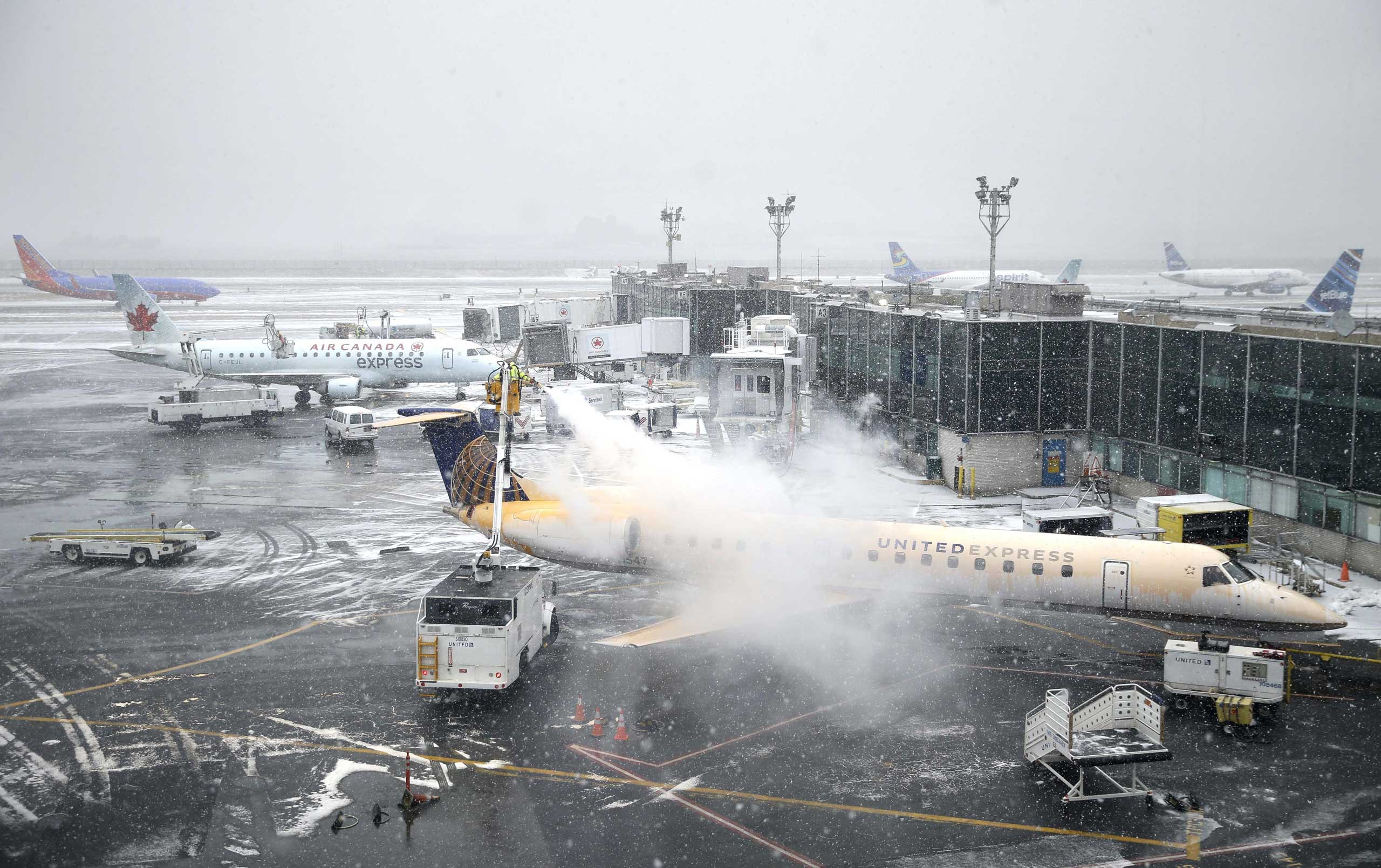 A plane is de-iced at LaGuardia Airport in New York City on Jan. 26, 2015.