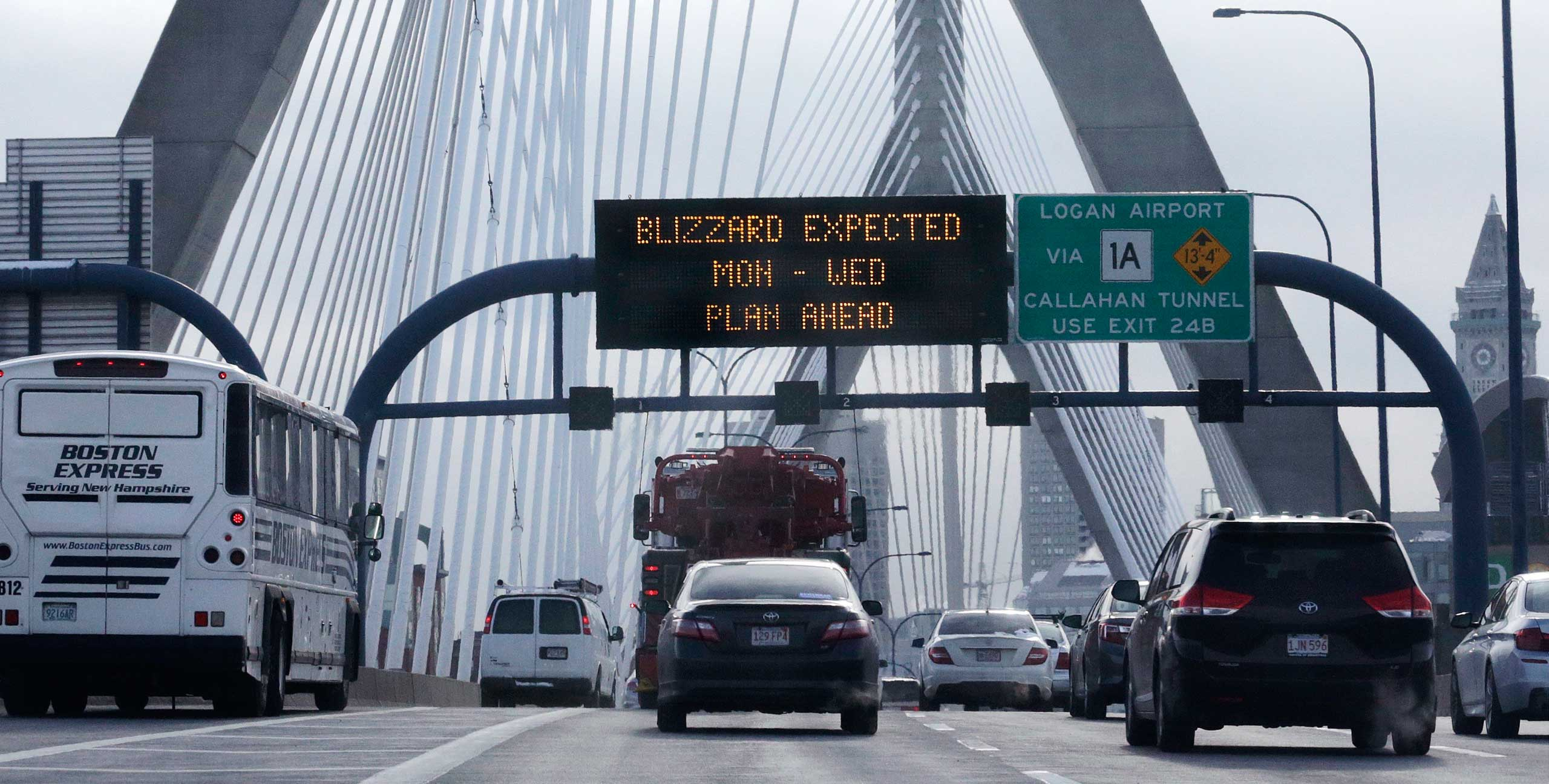 With a road sign warning of an expected blizzard, morning commuters travel across the Zakim Bunker Hill Bridge into downtown Boston, Jan. 26, 2015.