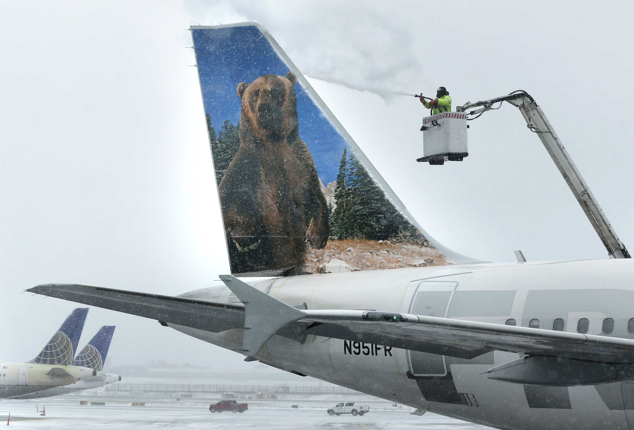 A crewmember de-ices a Frontier Airlines plane at LaGuardia Airport in New York City, Jan. 26, 2015.