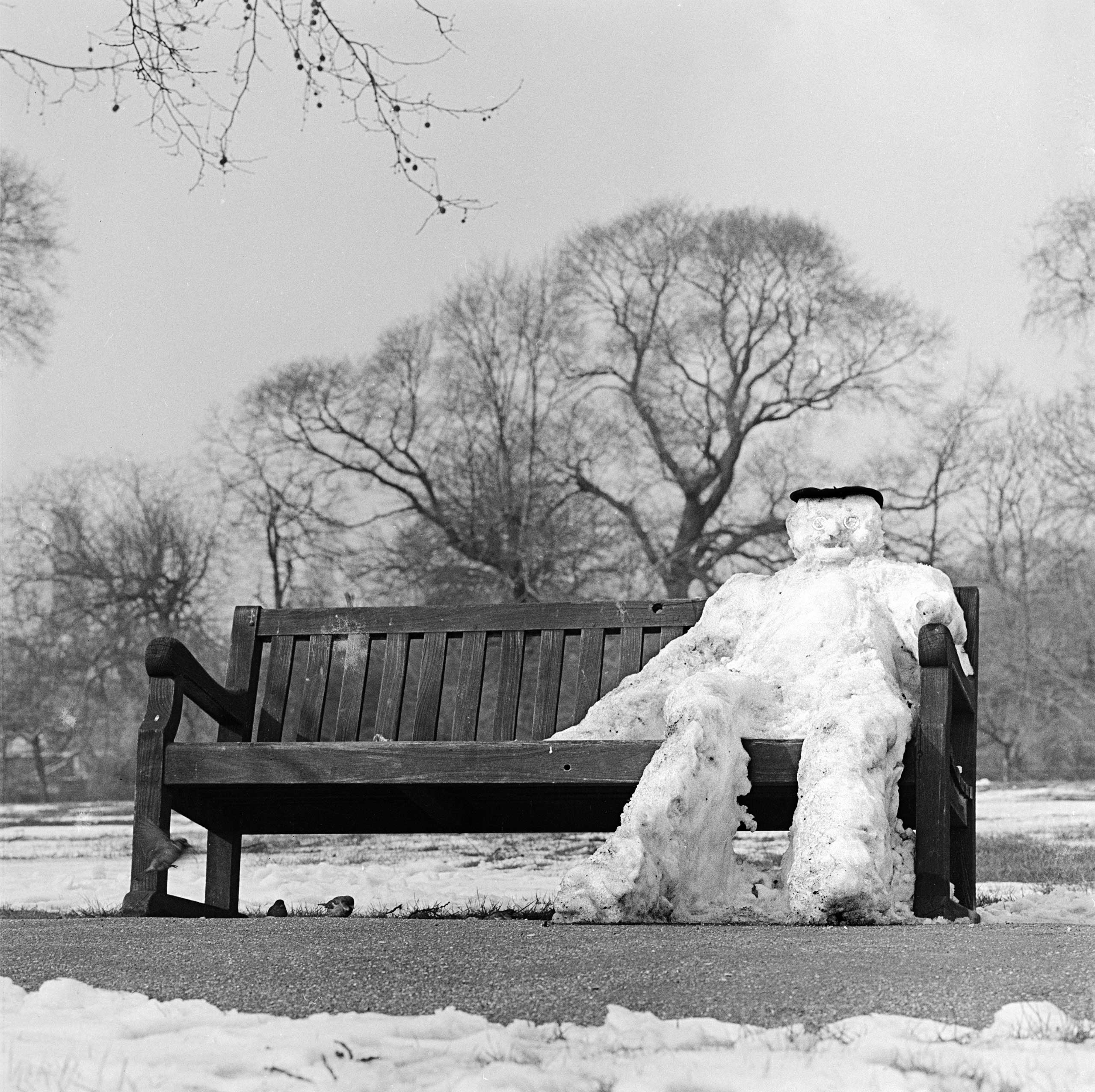 A snowman sitting on a park bench in London, circa 1960