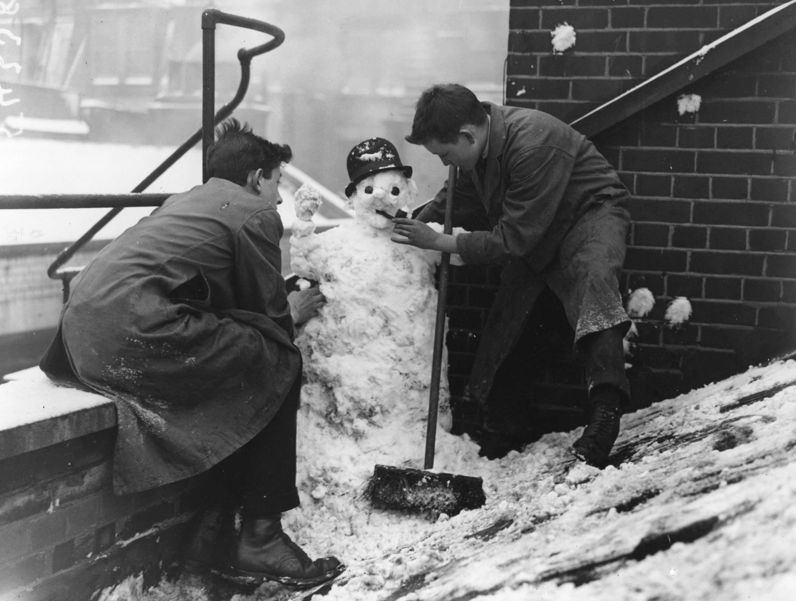 Two boys making a snowman, circa 1924