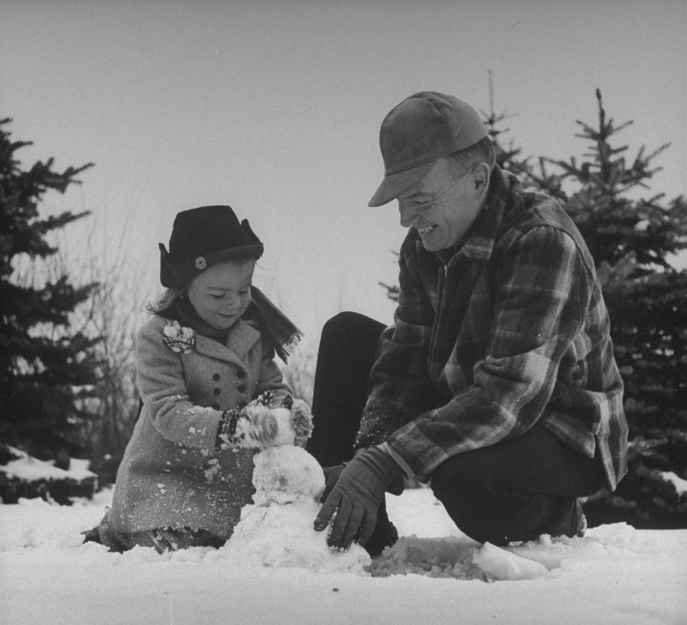 Harold E. Stassen (R) building a snowman with his daughter in 1945
