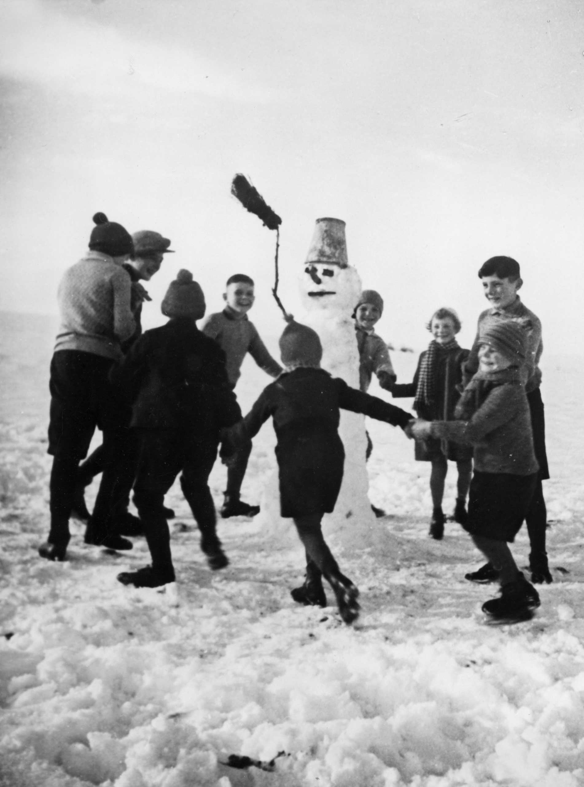 Children dance around a snowman on Dec. 10, 1937, in Austria