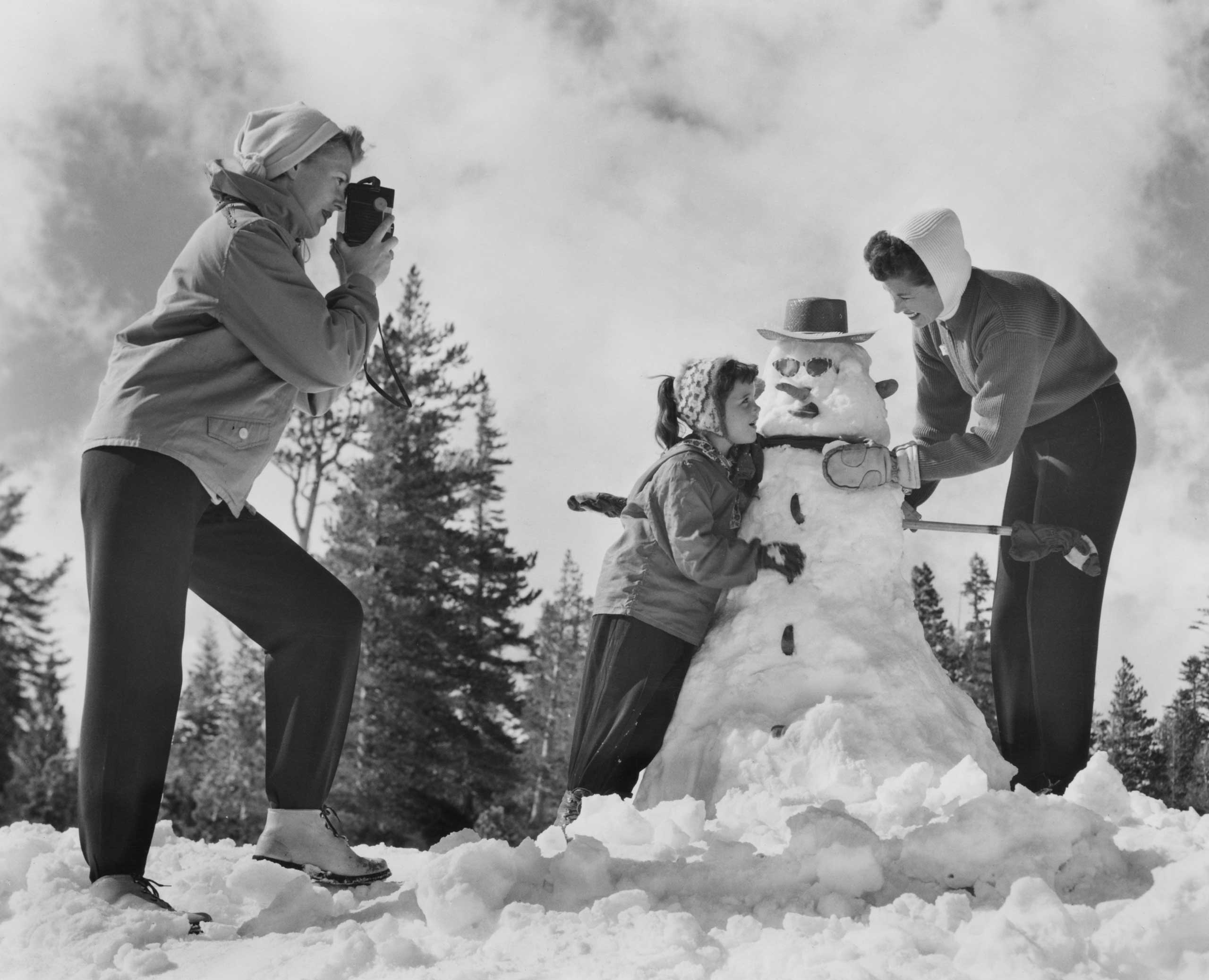 Two women help a little girl complete her snowman, circa 1955.
