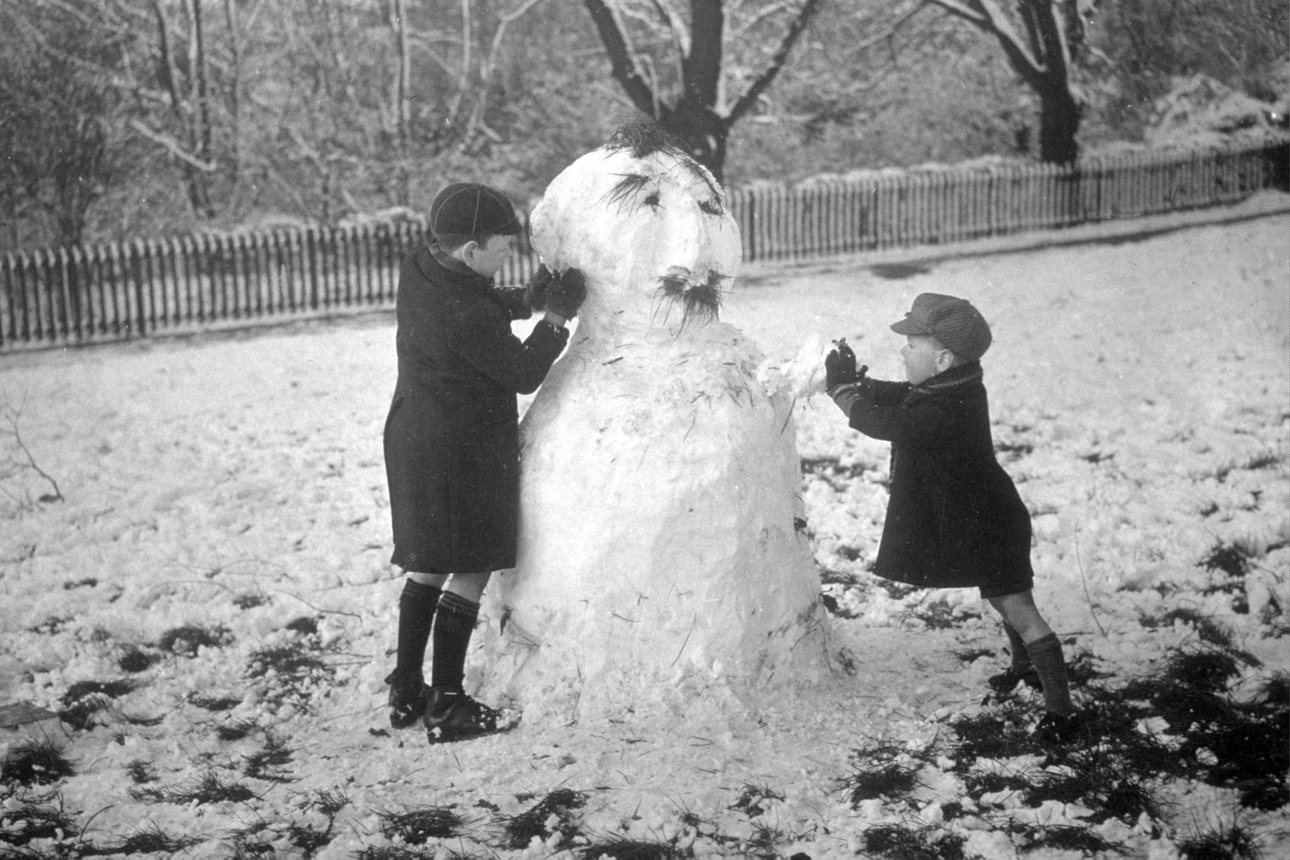 Two children making a snowman complete with 'hair' in Finsbury Park, London, circa 1935