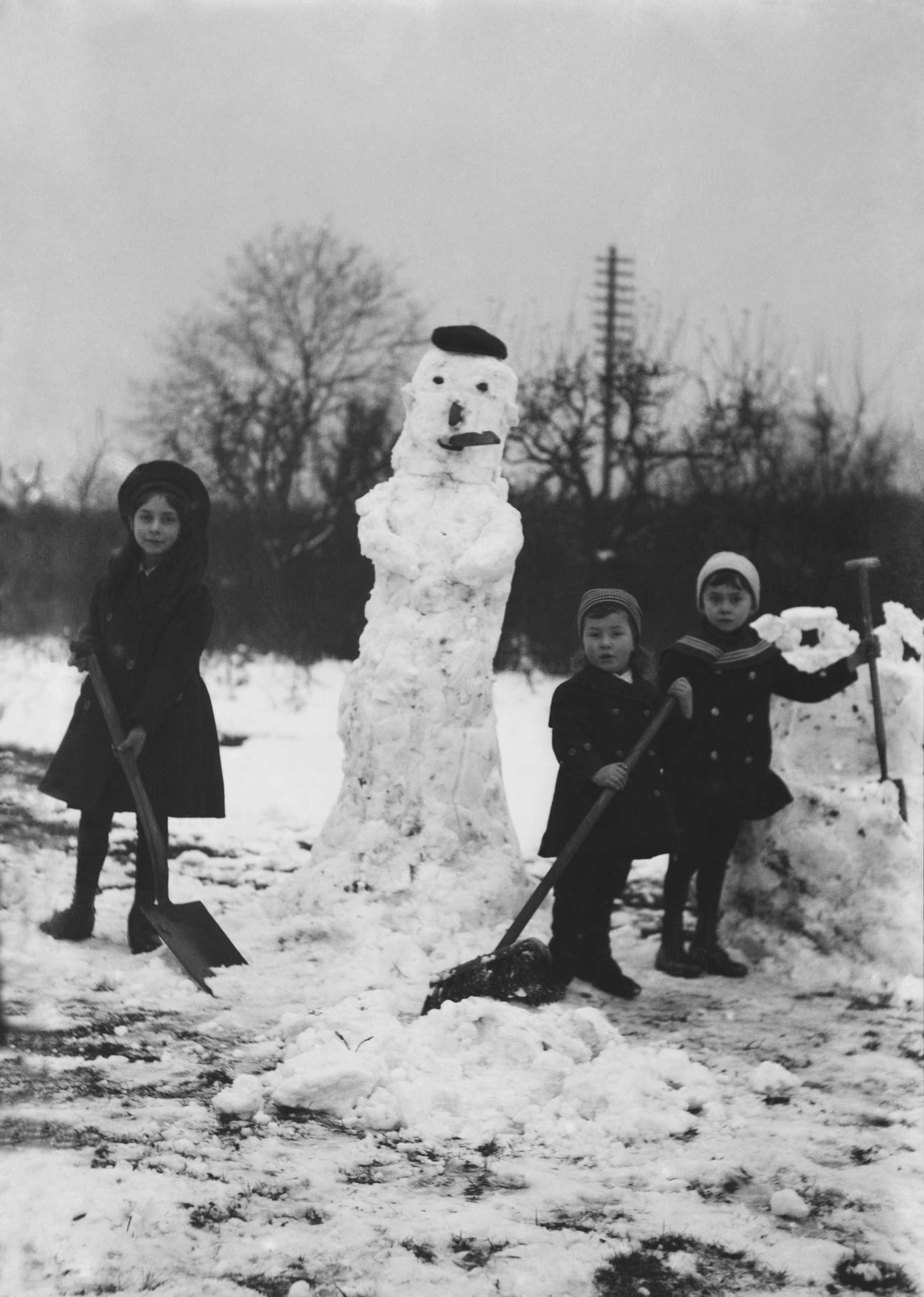 A group of young children wrapped up warmly, holding shovels and a broom building snowmen in a snow covered field; Europe circa 1900.