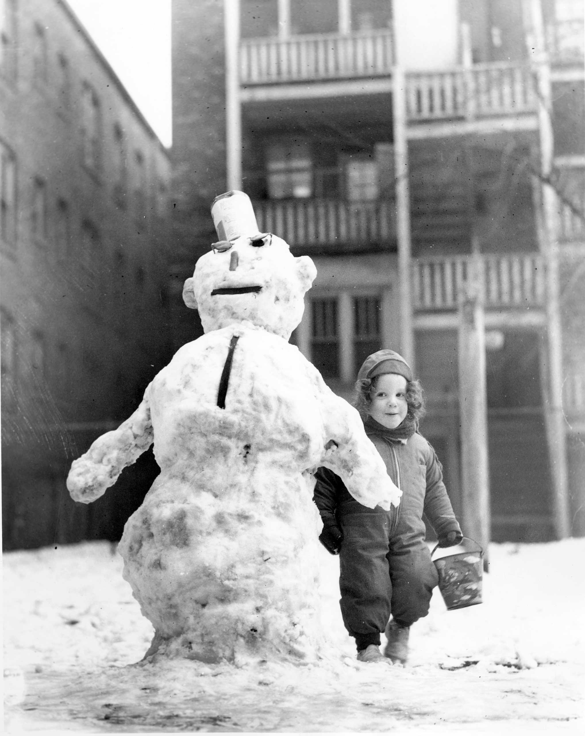 Mary Andrea Arnold in a snowsuit next to a snowman in Chicago on Jan. 17, 1943.