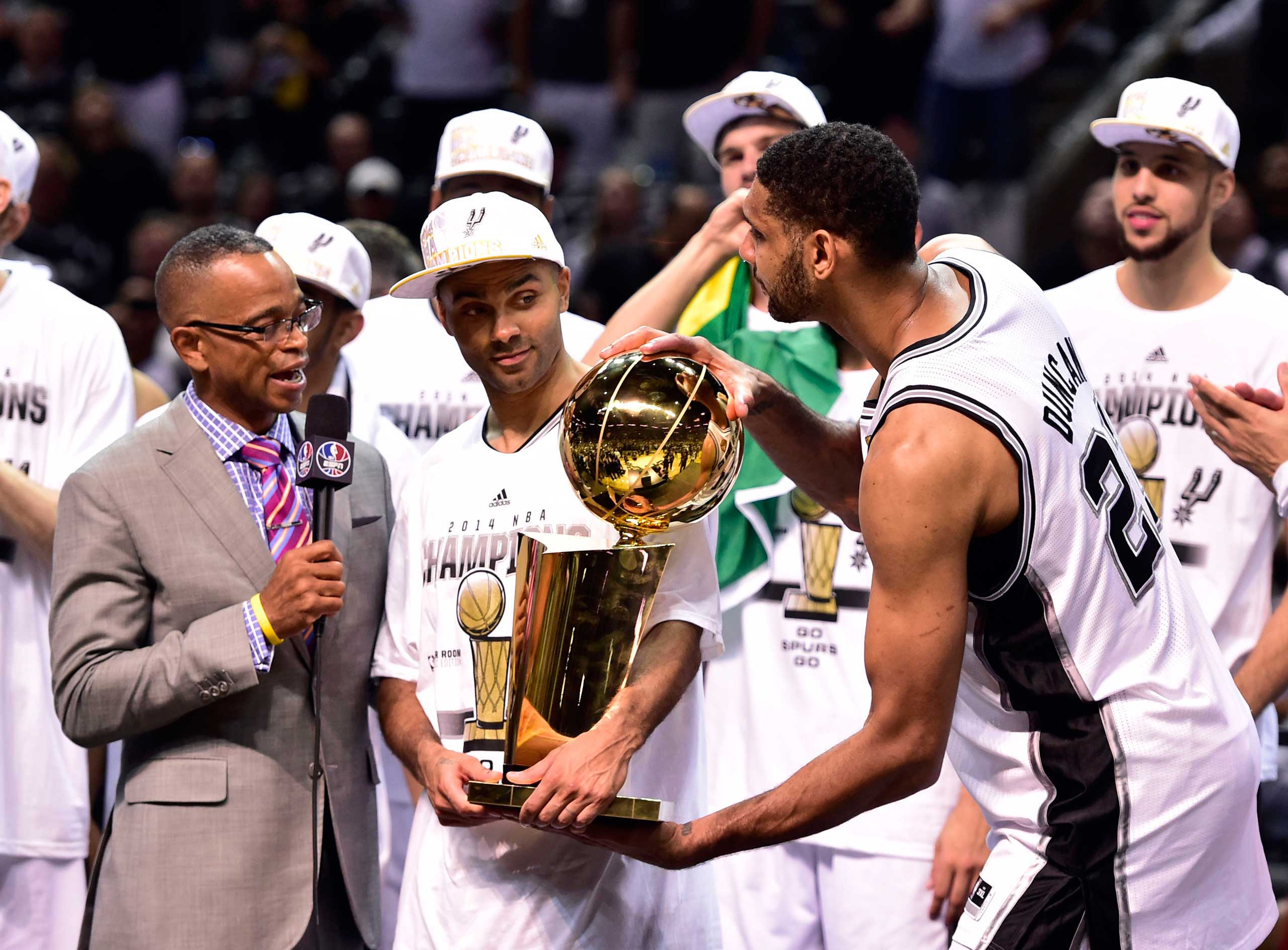San Antonio Spurs forward Tim Duncan takes the Larry O'Brian Trophy from guard Tony Parker  as he does a TV interview with Scott after game five of the 2014 NBA Finals against the Miami Heat at AT&T Center on June 15, 2014.