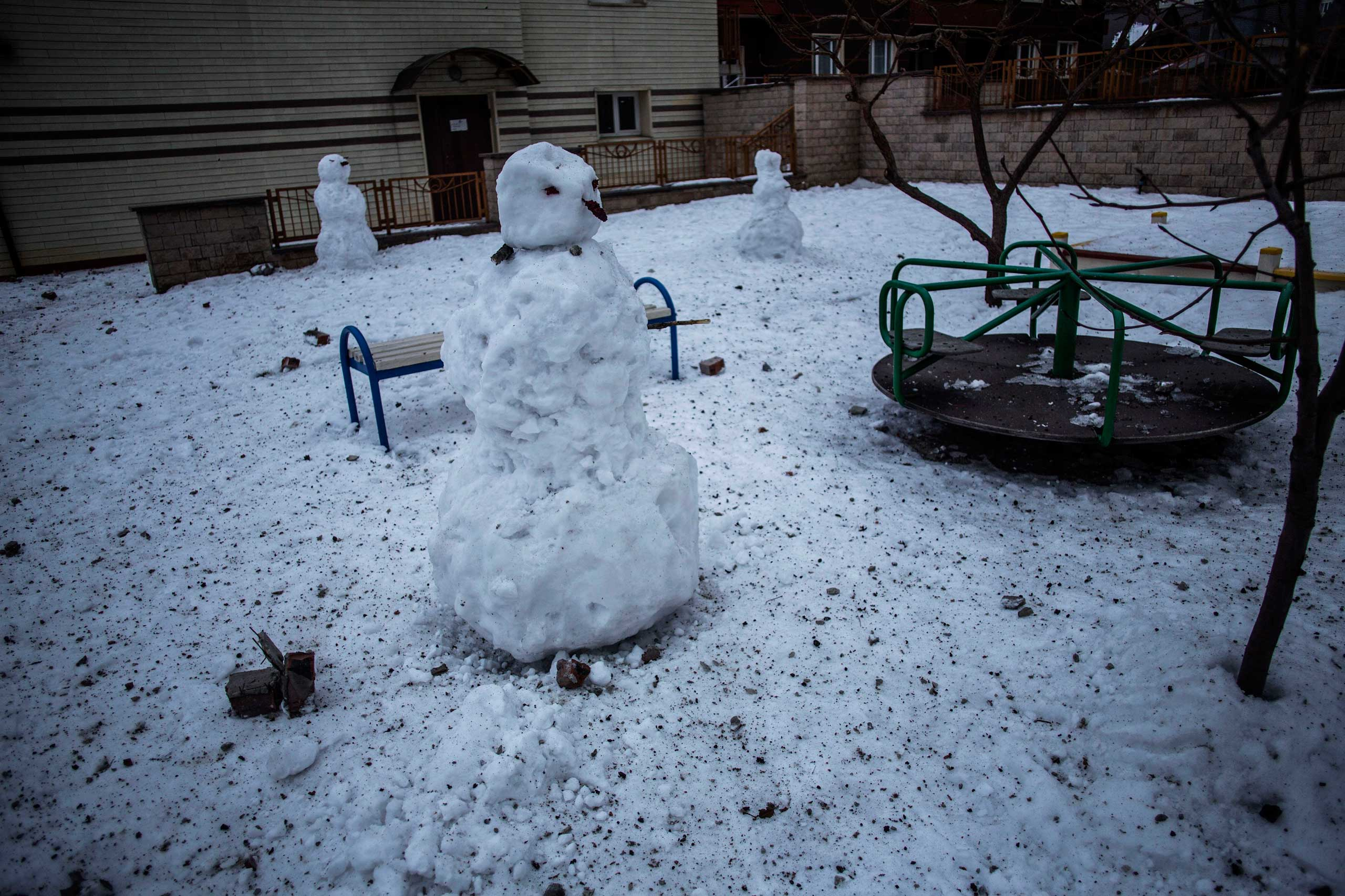 Snowmen hit by shrapnel and debris are seen in a deserted playground in the Voroshilovsky area,  in the center of Donetsk, Ukraine. Sunday, Jan. 18, 2015.
