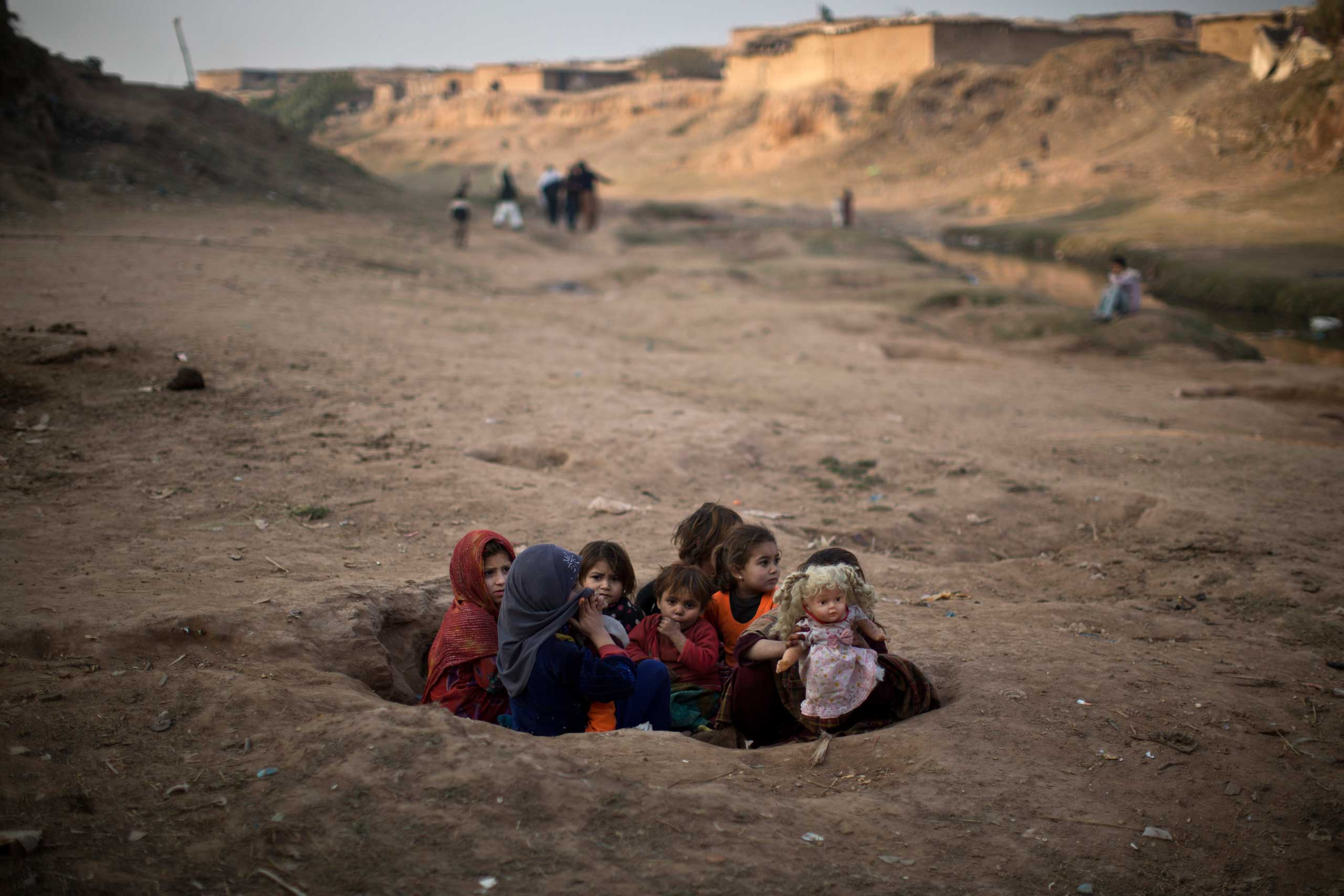 Afghan refugee girls sit in a hole in the ground, playing with a doll in a slum areas on the outskirts of Islamabad, Pakistan, Saturday, Jan. 3, 2015.