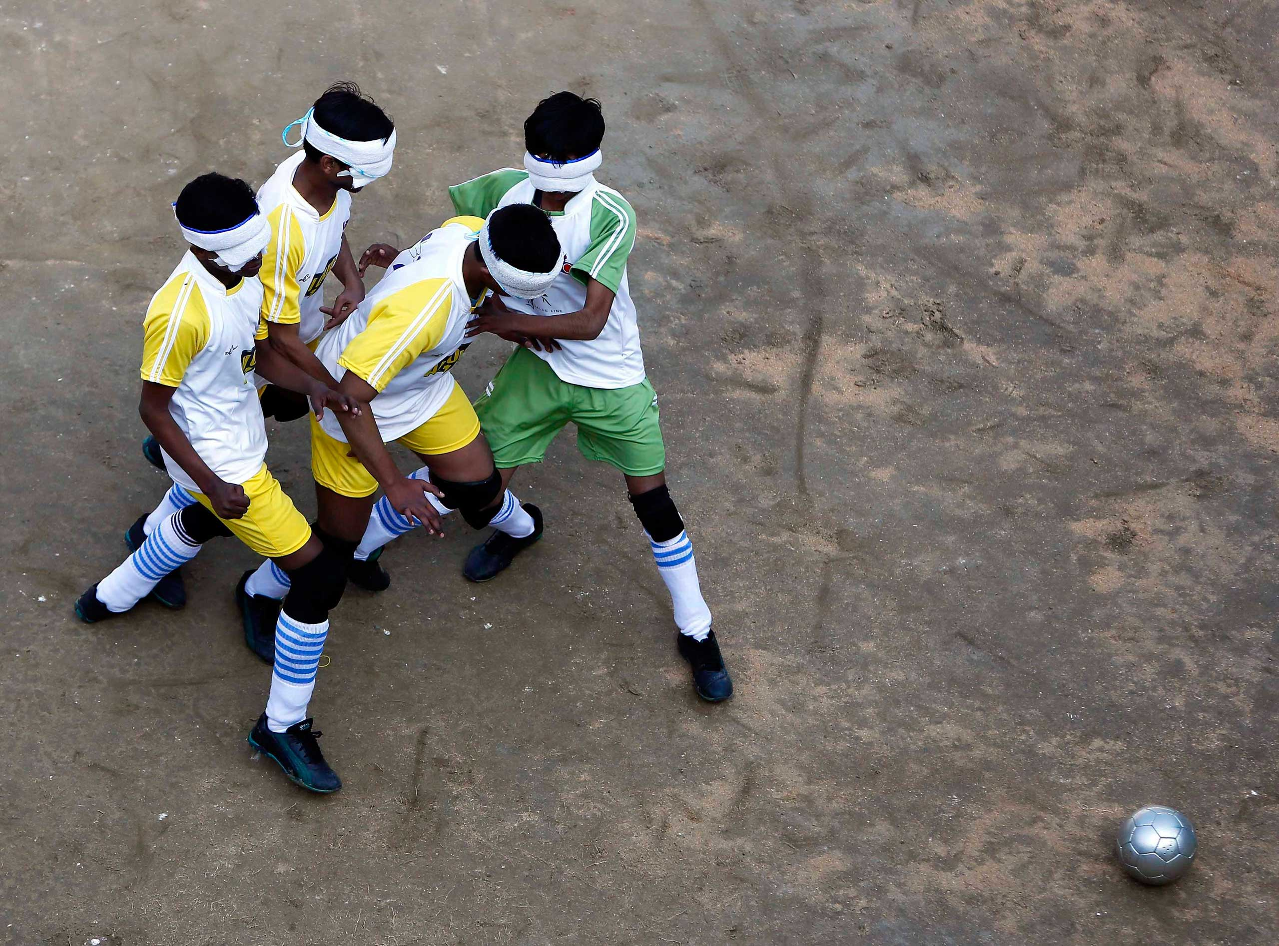 Visually impaired students of a school for the blind fight for the ball during a soccer match inside their school in New Delhi Jan. 5, 2015.