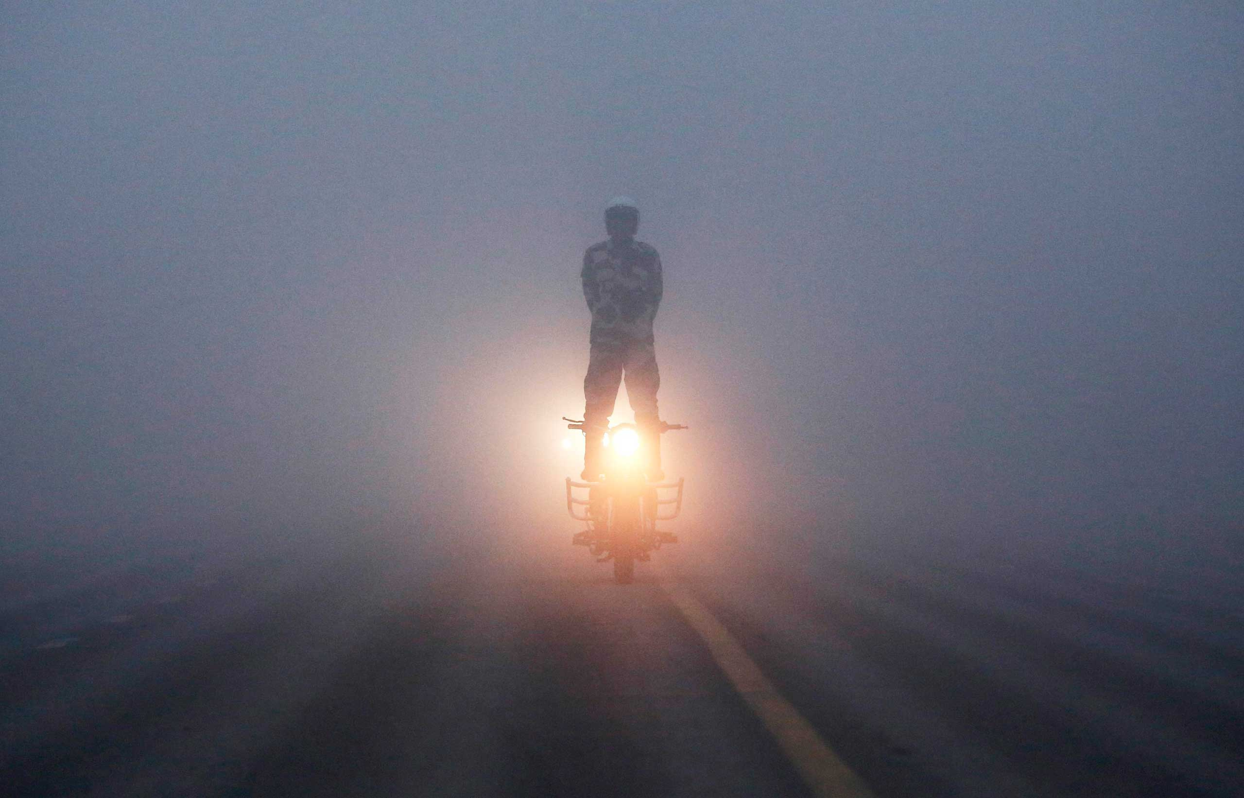 An India's Border Security Force (BSF)  Daredevils  motorcycle rider performs during a rehearsal for the Republic Day parade on a foggy winter morning in New Delhi Jan. 8, 2015.