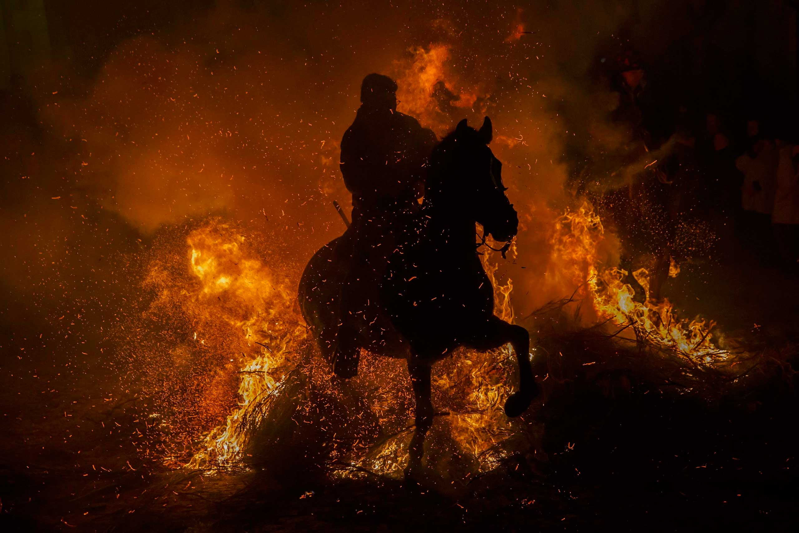 A man rides his horse through flames during the  Luminarias  annual religious celebration, on the night before Saint Anthony's, patron of animals, in the village of San Bartolome de los Pinares, Spain, Jan.16, 2015.
