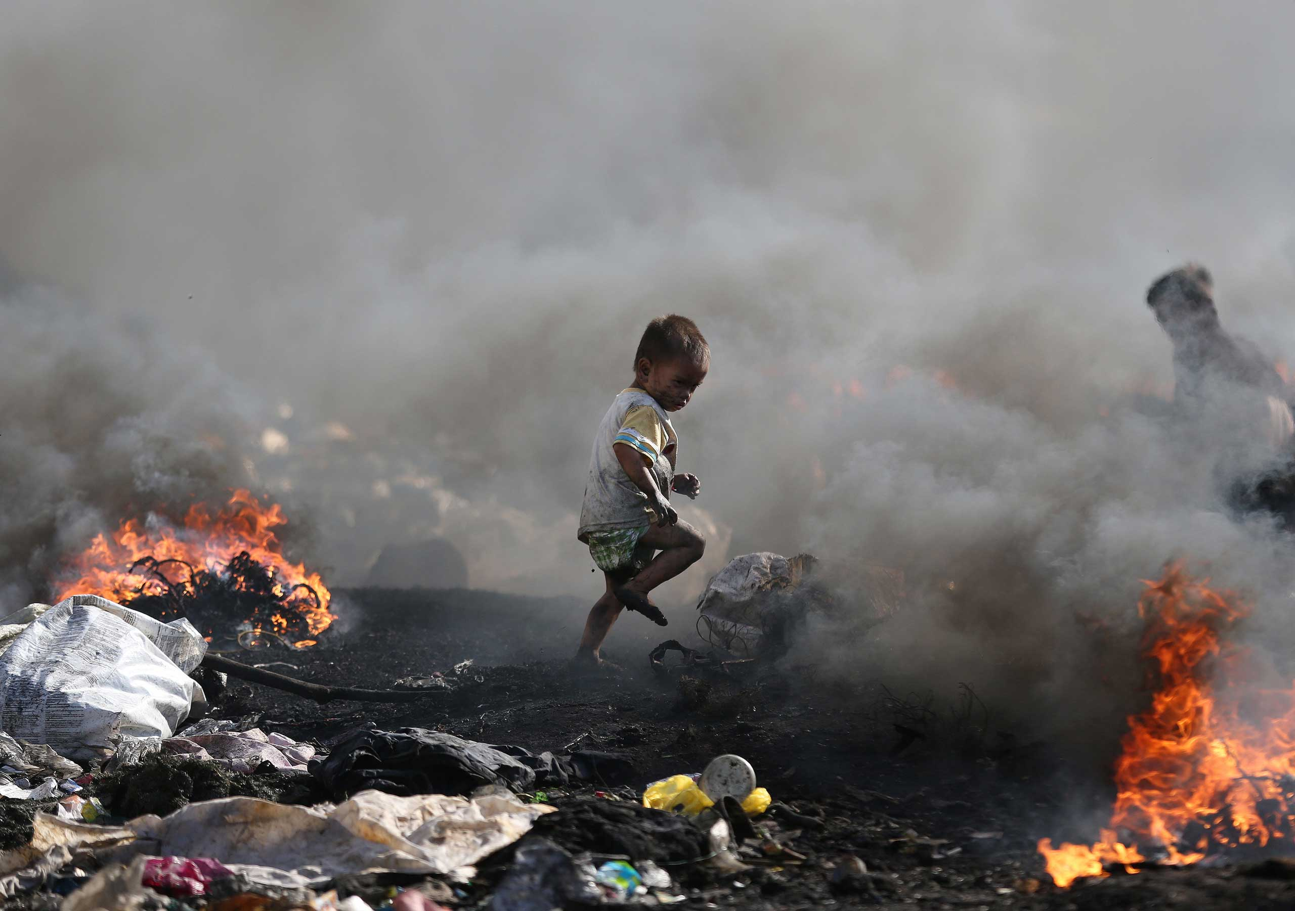 A Filipino boy runs amid black smoke billowing from electrical wires being burned by scavengers at a dumpsite in Manila, Philippines, Jan. 8, 2015.