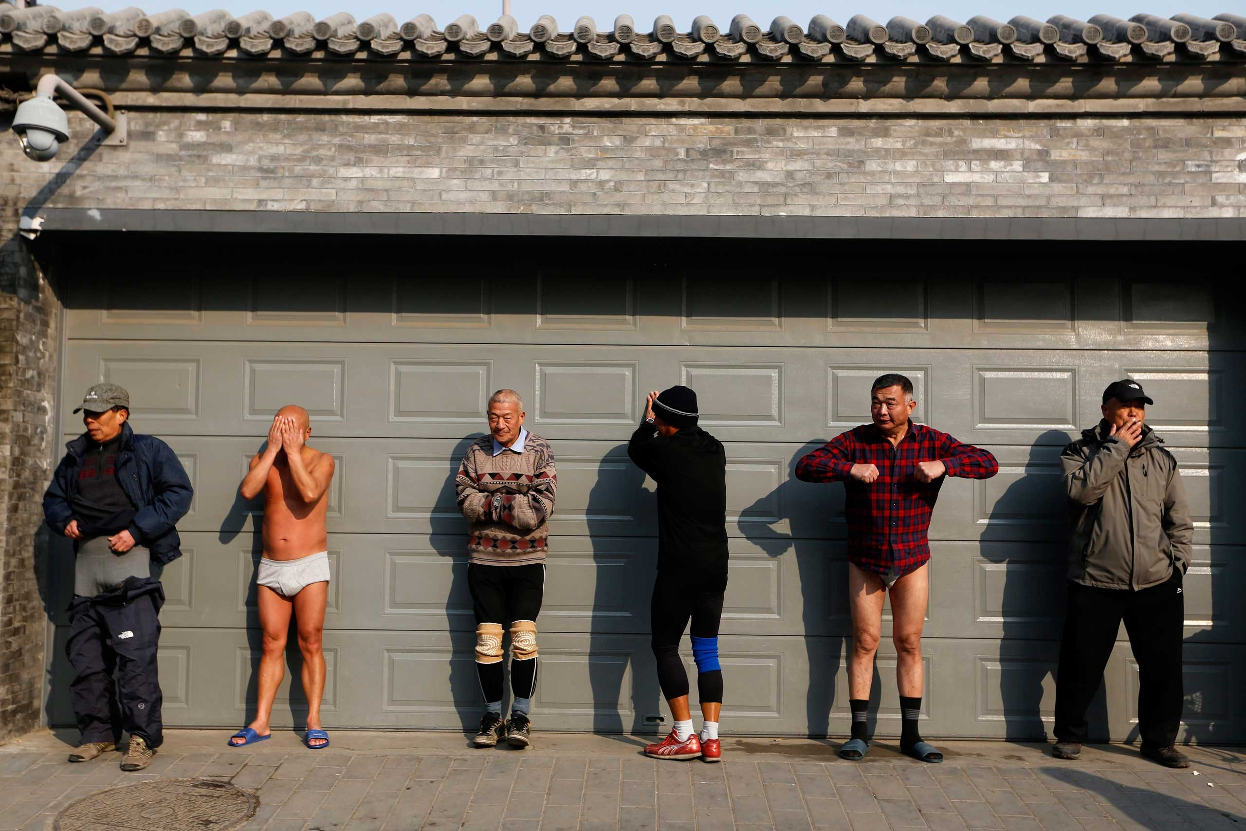 Chinese winter swimming enthusiasts warm up before swimming in the half-frozen Houhai lake with a water temperature around two degrees Celsius in Beijing, China, Jan. 12 2015.