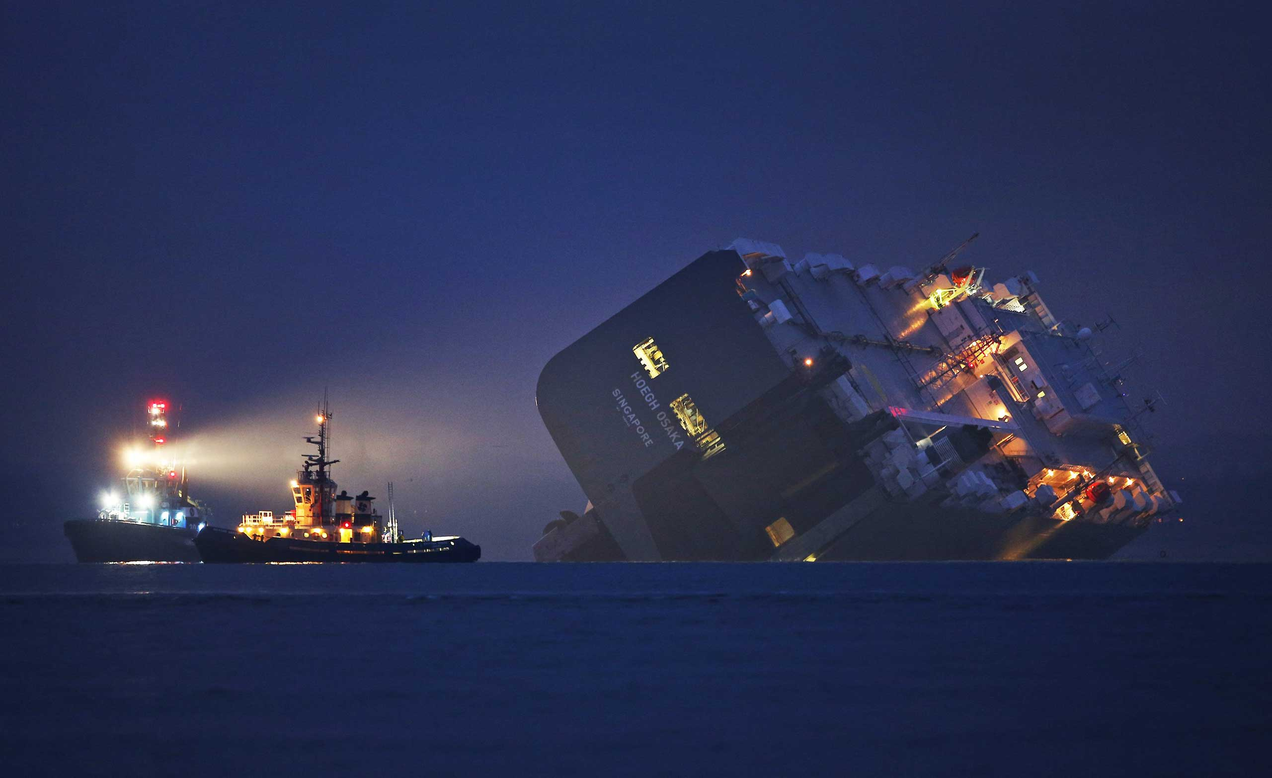 A salvage tug lights the hull of the stricken Hoegh Osaka cargo ship after it ran aground on a sand bank in the Solent on Jan.4, 2015 in Cowes, England.