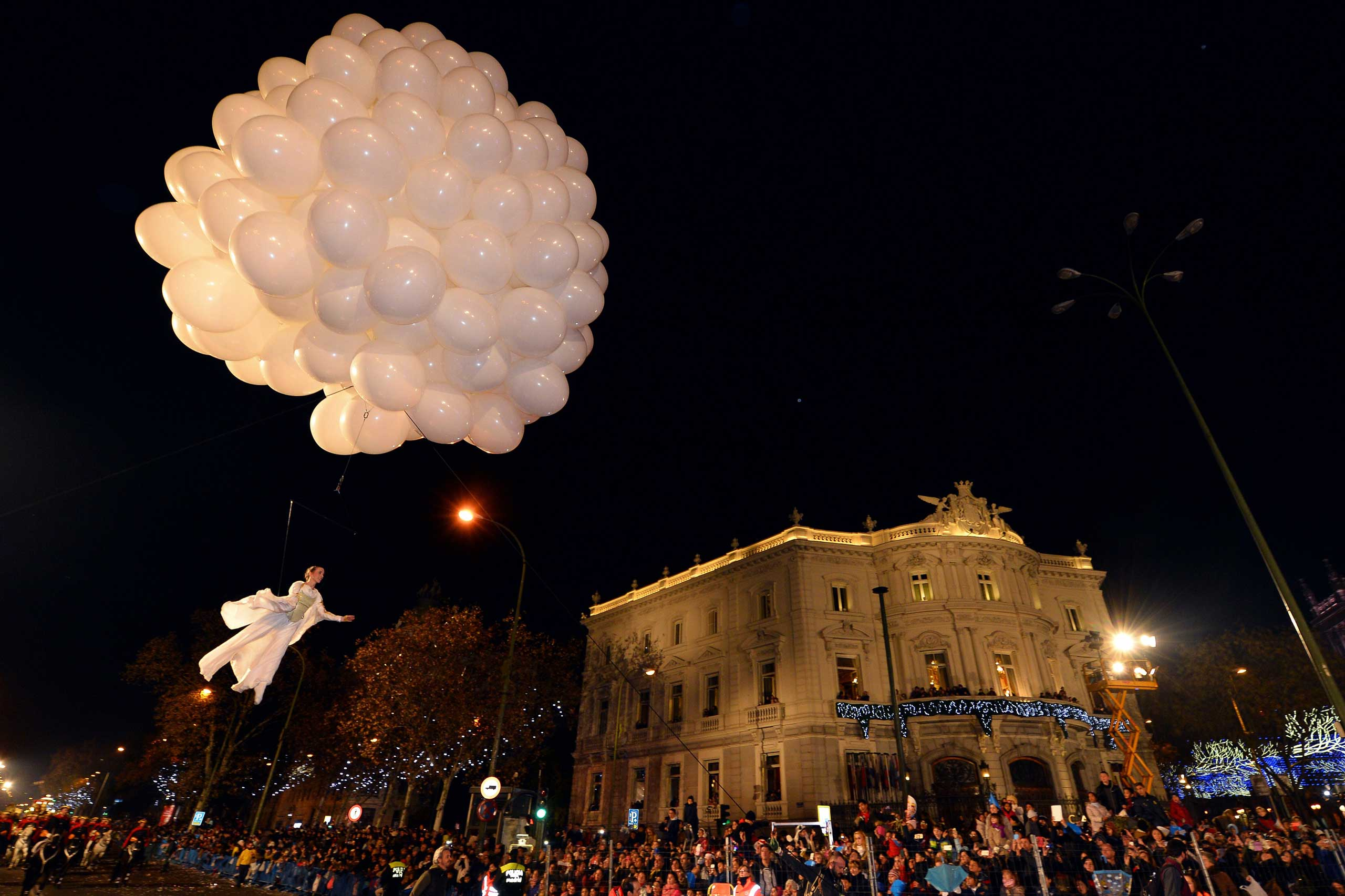 An artist performs in the air with balloons at Cibeles Square during the Three Kings parade in Madrid on Jan. 5, 2015.