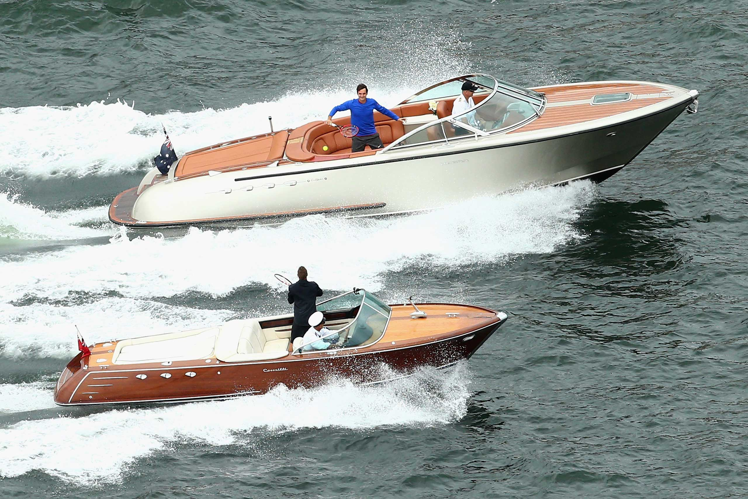 Roger Federer of Switzerland plays tennis with Lleyton Hewitt of Australia between speedboats on Sydney Harbour ahead of their Fast 4 Exhibition match on Jan. 12, 2015 in Sydney, Australia.