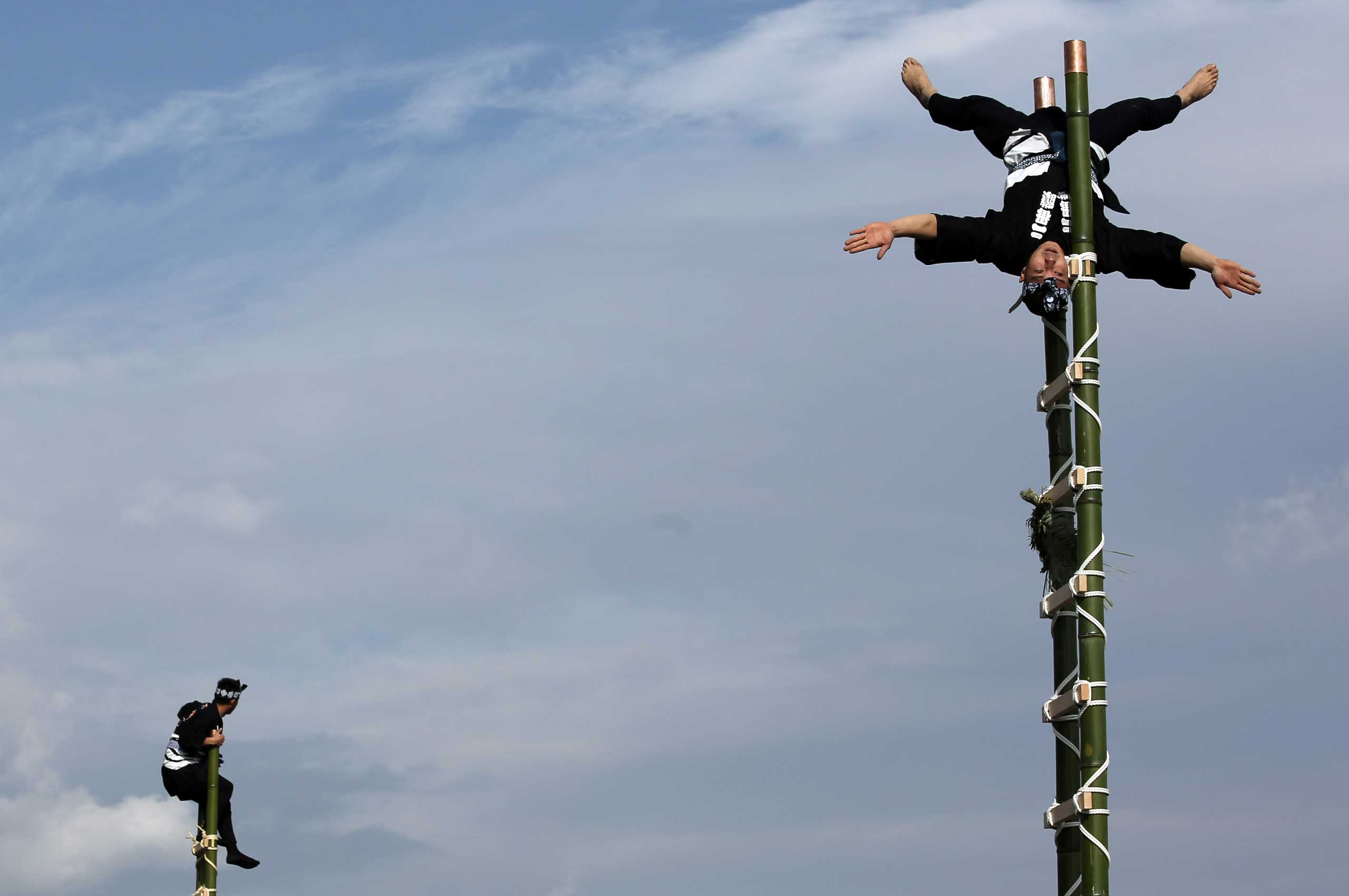 Members of a traditional firefighting preservation group perform ladder stunts during the annual New Year's Fire Brigade Review in Tokyo,  Jan. 6, 2015.