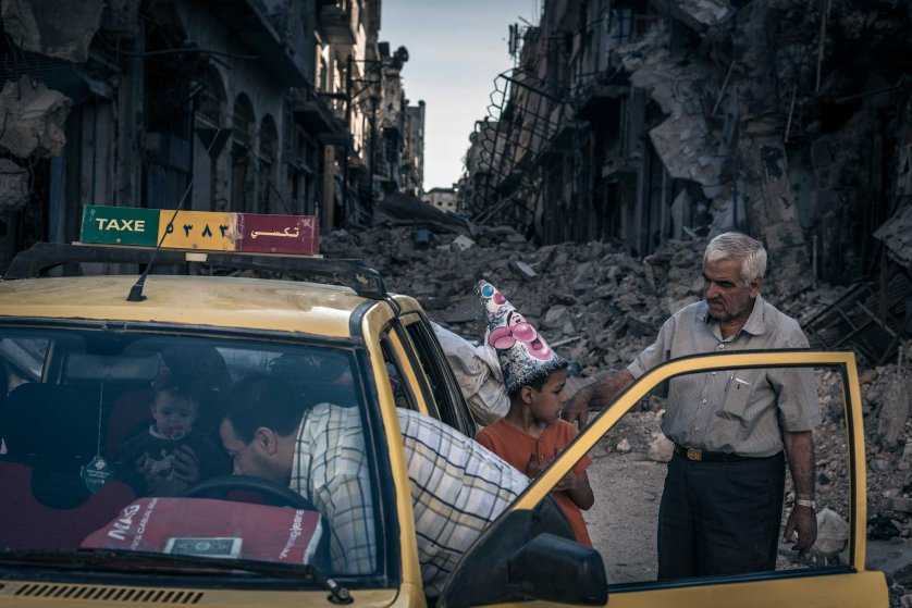 Abu Hisham Abdel Karim loads a taxi with his belongings in the Khalidieh district of Homs, Syria, which had been destroyed by fighting.