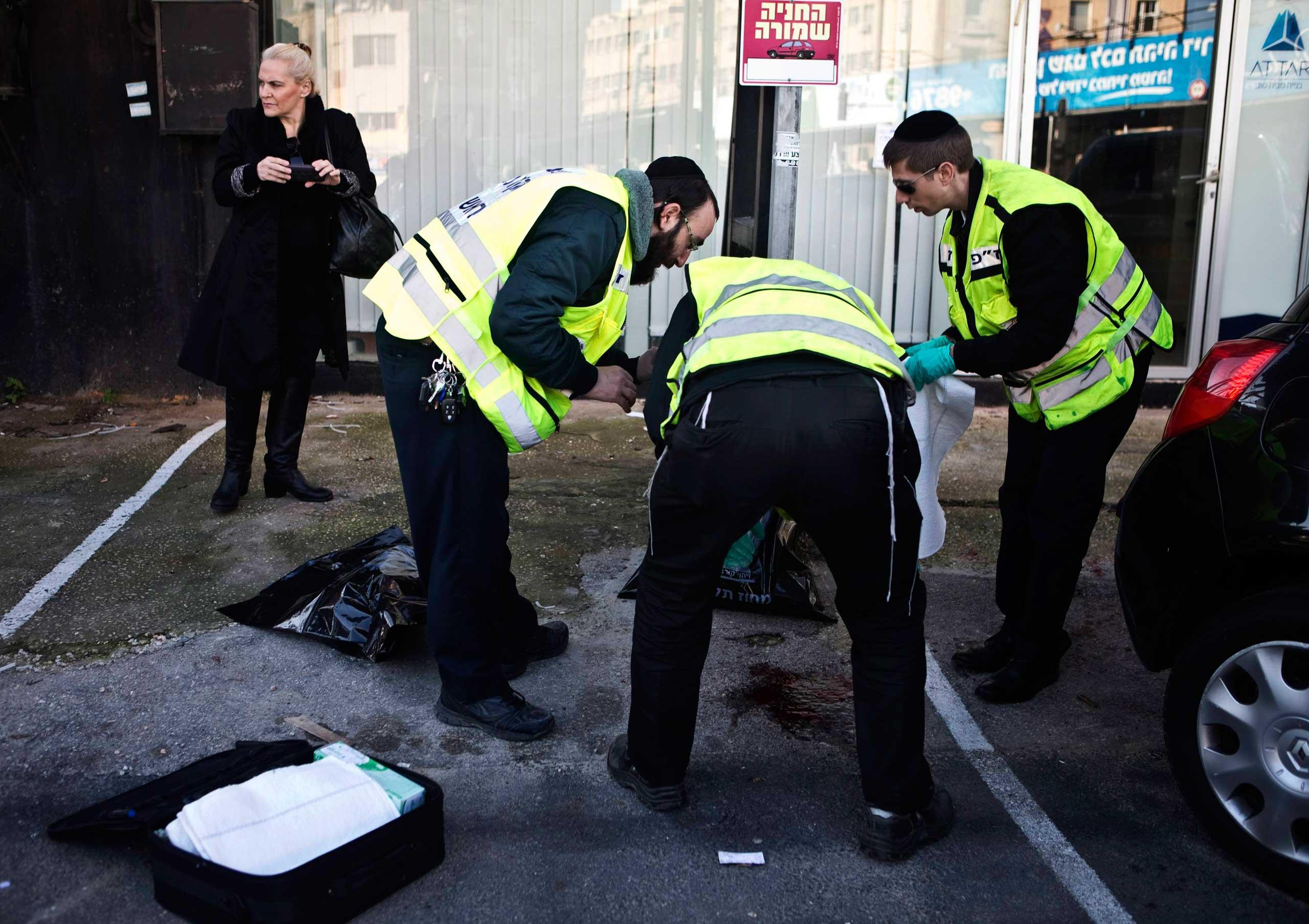 Members of the Israeli Zaka emergency response team survey the scene of a stabbing attack in Tel Aviv, Jan. 21, 2015.