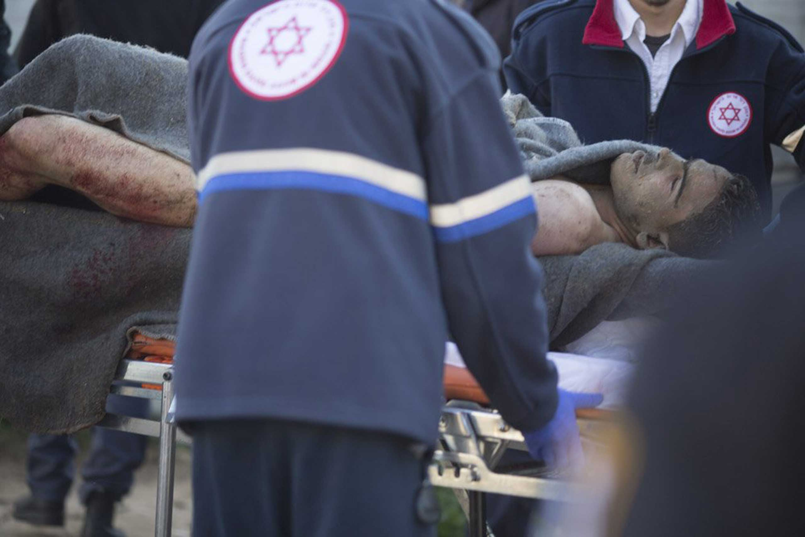 Israeli police carry the injured suspect on a stretcher as they attend the scene of a stabbing attack on Jan. 21, 2015 in Tel Aviv.