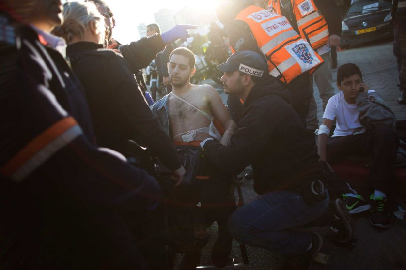 An Israeli police officer and paramedics treat an injured man at the scene of a stabbing in Tel Aviv, Jan. 21, 2015.
