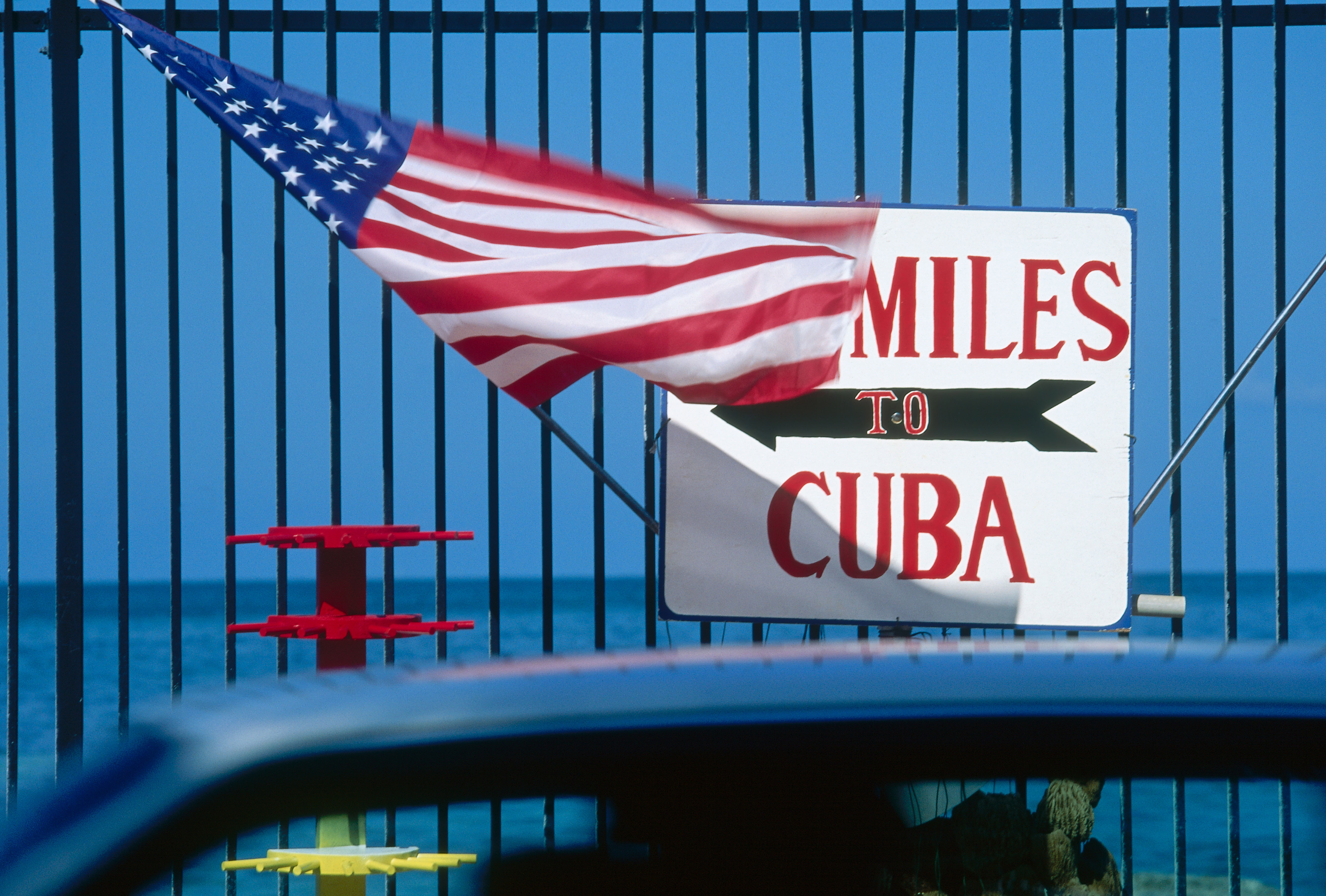 American flag with signboard of Cuba Southernmost Point, Key West, Fla.