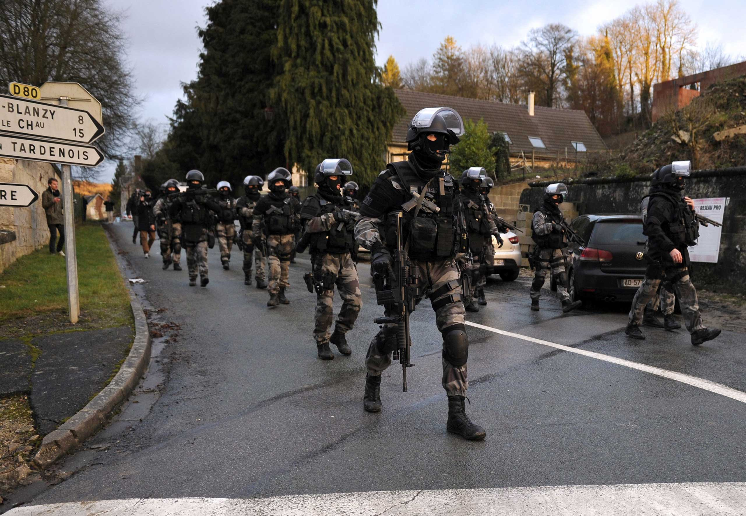 TOPSHOTS                        Members of the GIPN and RAID, French police special forces, walk in Corcy, northern France, on January 8, 2015 as they carry out searches as part of an investigation into a deadly attack the day before by armed gunmen on the Paris offices of French satirical weekly Charlie Hebdo. A huge manhunt for two brothers suspected of massacring 12 people in an Islamist attack at a satirical French weekly zeroed in on a northern town on January 8 after the discovery of one of the getaway cars. As thousands of police tightened their net, the country marked a rare national day of mourning for January 7's bloodbath at Charlie Hebdo magazine in Paris, the worst terrorist attack in France for half a century.   AFP PHOTO / FRANCOIS LO PRESTIFRANCOIS LO PRESTI/AFP/Getty Images