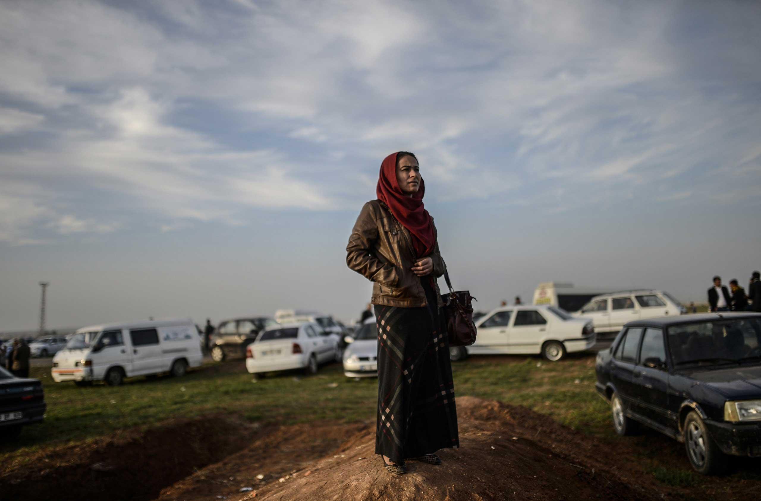 A Kurdish woman stands near the Turkish-Syrian border in Suruc, Turkey, on Jan. 27, 2015.